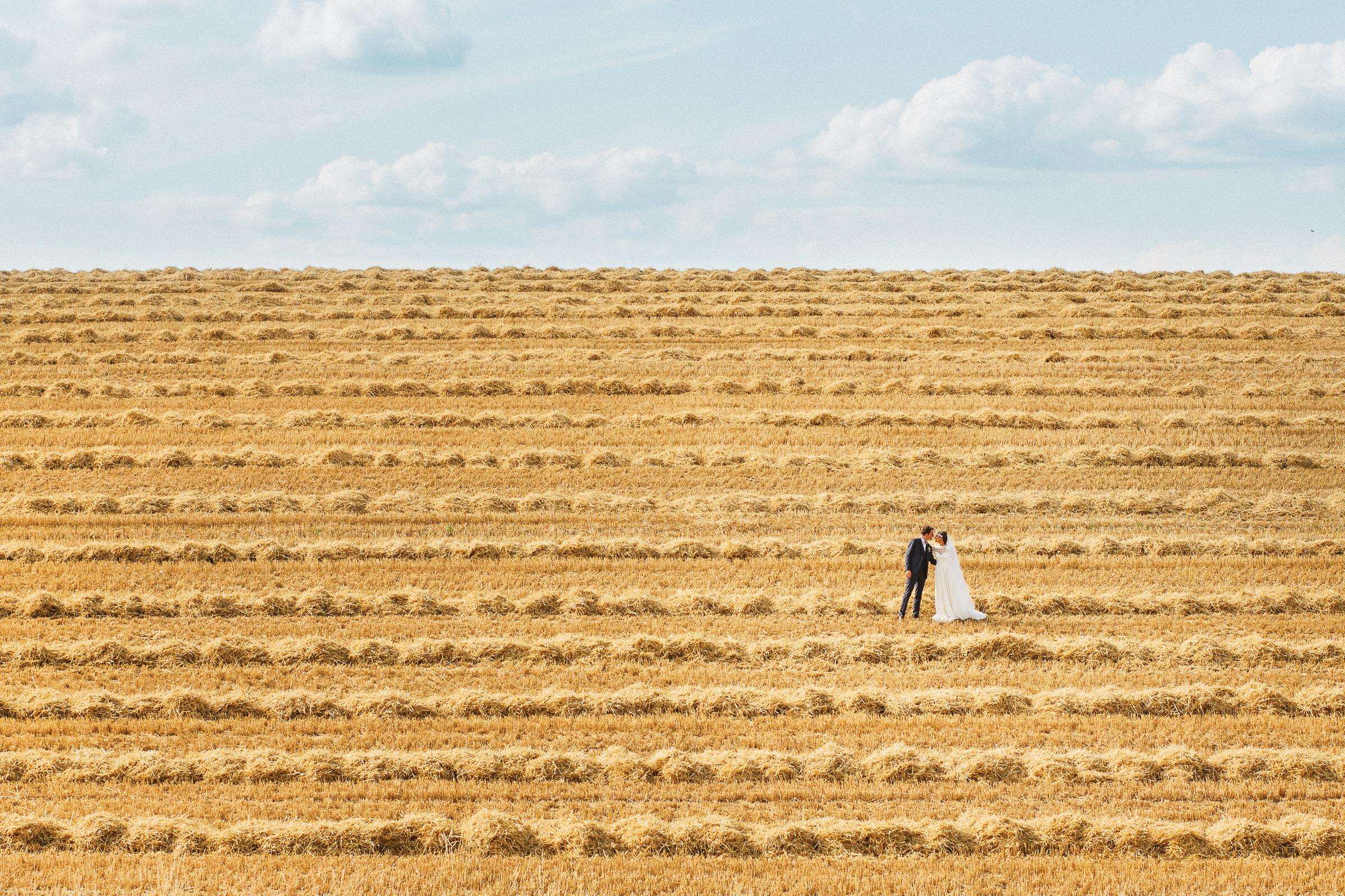 Landscape couple in hay field - photo by Sylvain Bouzat Wedding Photographer