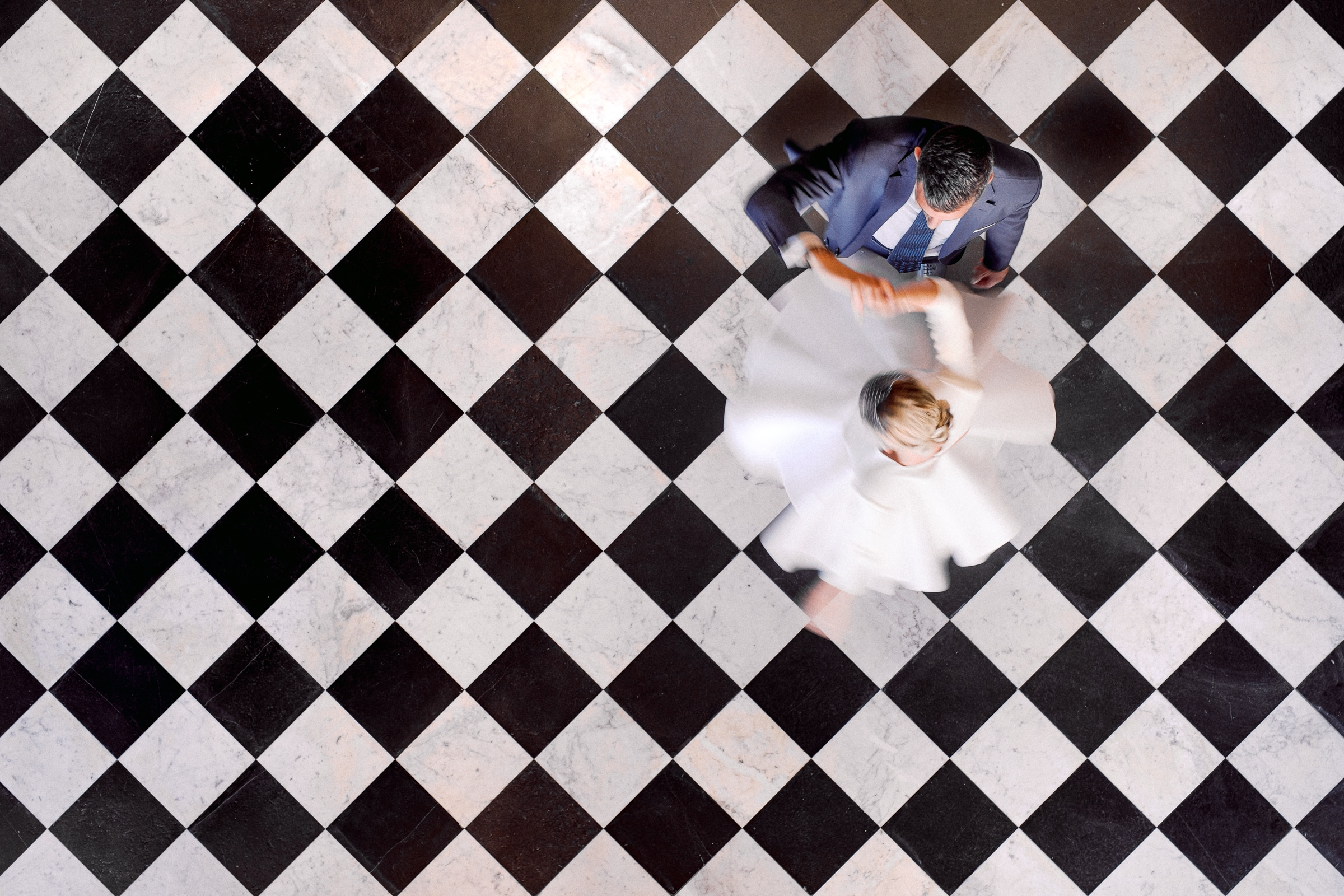 Top down shot of couple on checkered dance floor - photo by Sylvain Bouzat Wedding Photographer