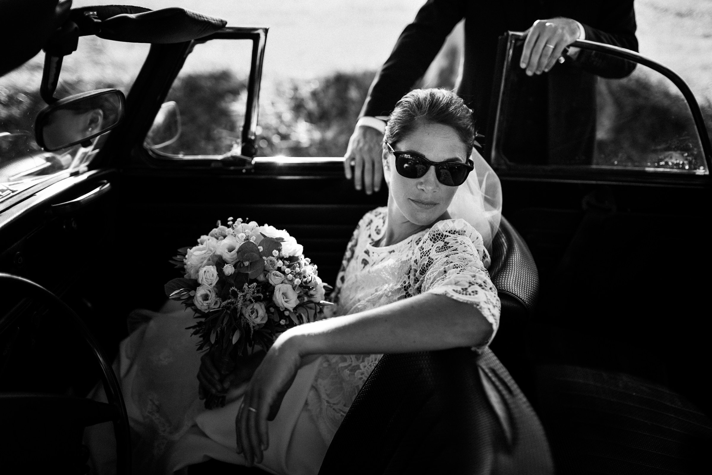 Bride wearing sun glasses in front seat of car - photo by Sylvain Bouzat Wedding Photographer