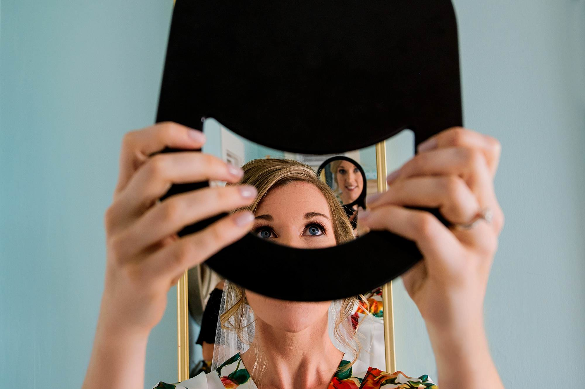 Bride getting ready reflected in mirrors - photo by Angela Nelson Photography