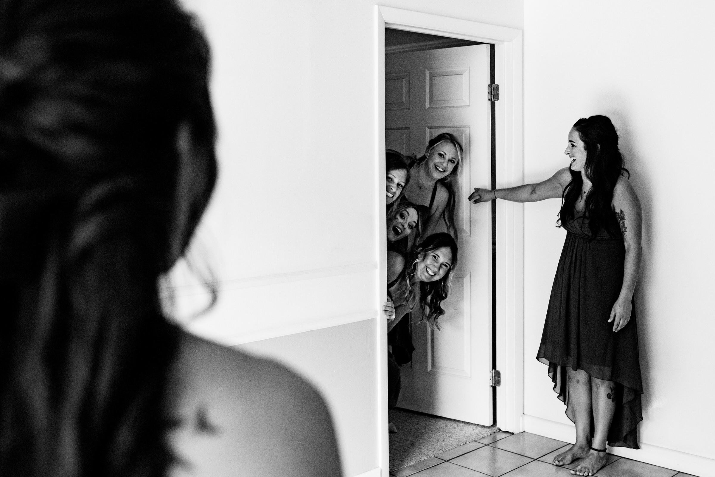 Bridesmaids peek in for first look at bride - photo by Angela Nelson Photography