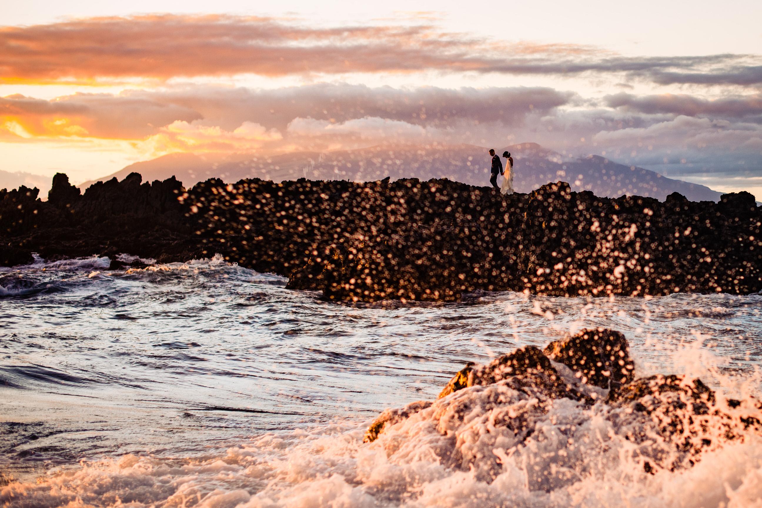 Couple against splashing surf - photo by Angela Nelson Photography