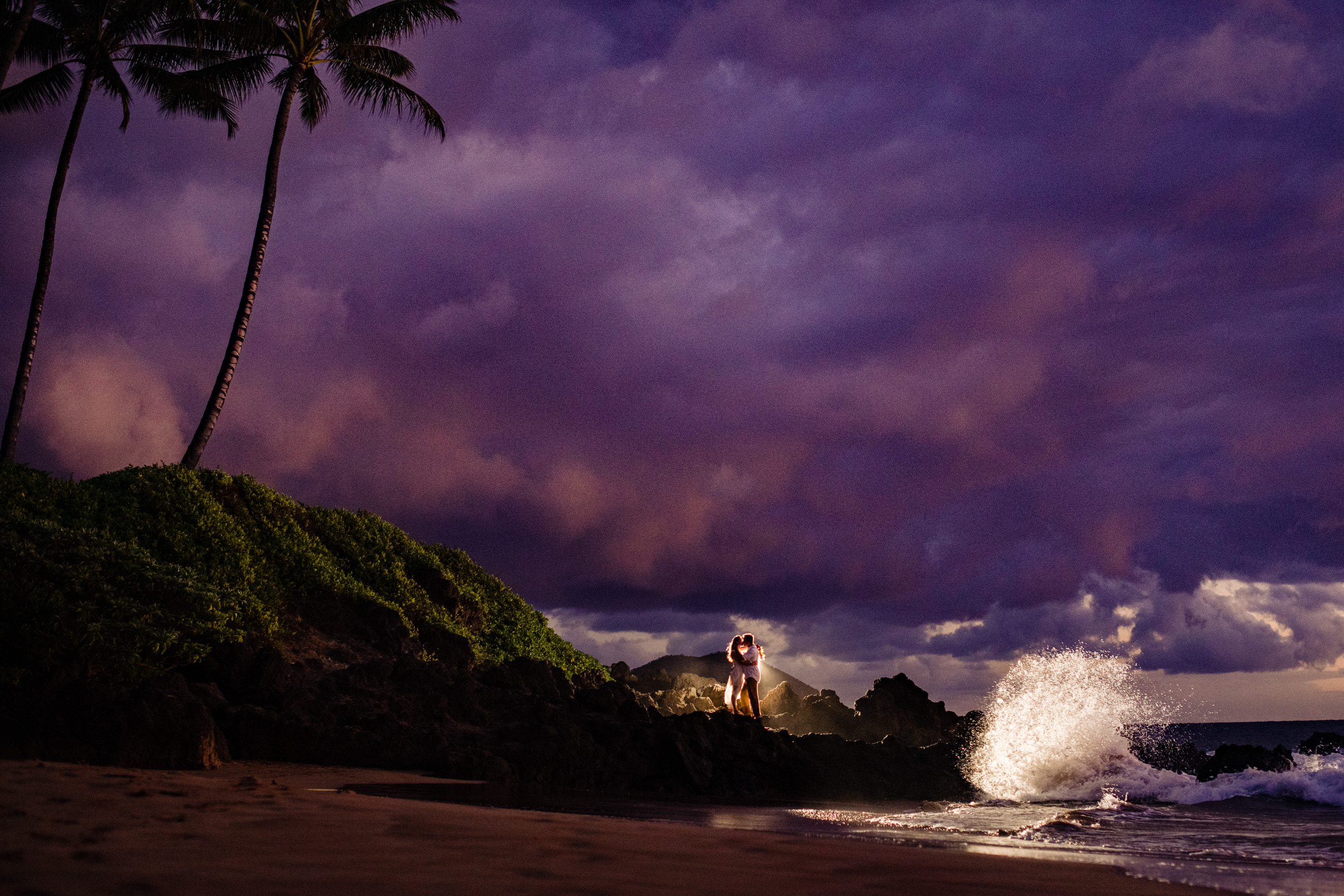 Couple at tropical surf against purple sky - photo by Angela Nelson Photography