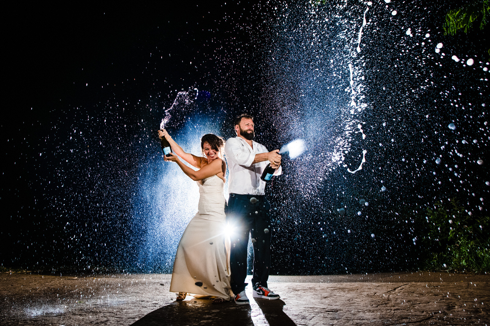 Couple in champagne spray - photo by Angela Nelson Photography