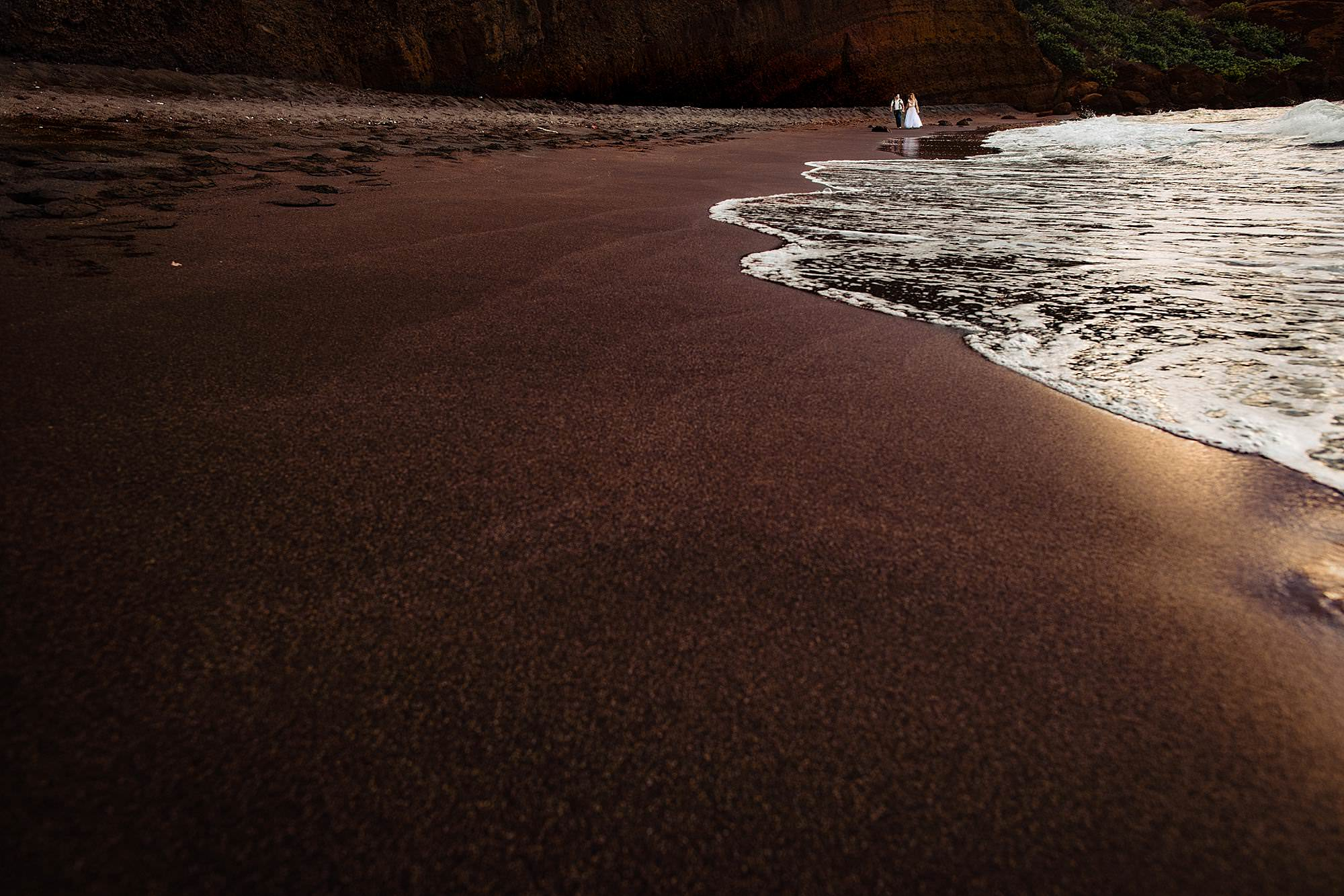 Couple walk at surfs edge - photo by Angela Nelson Photography