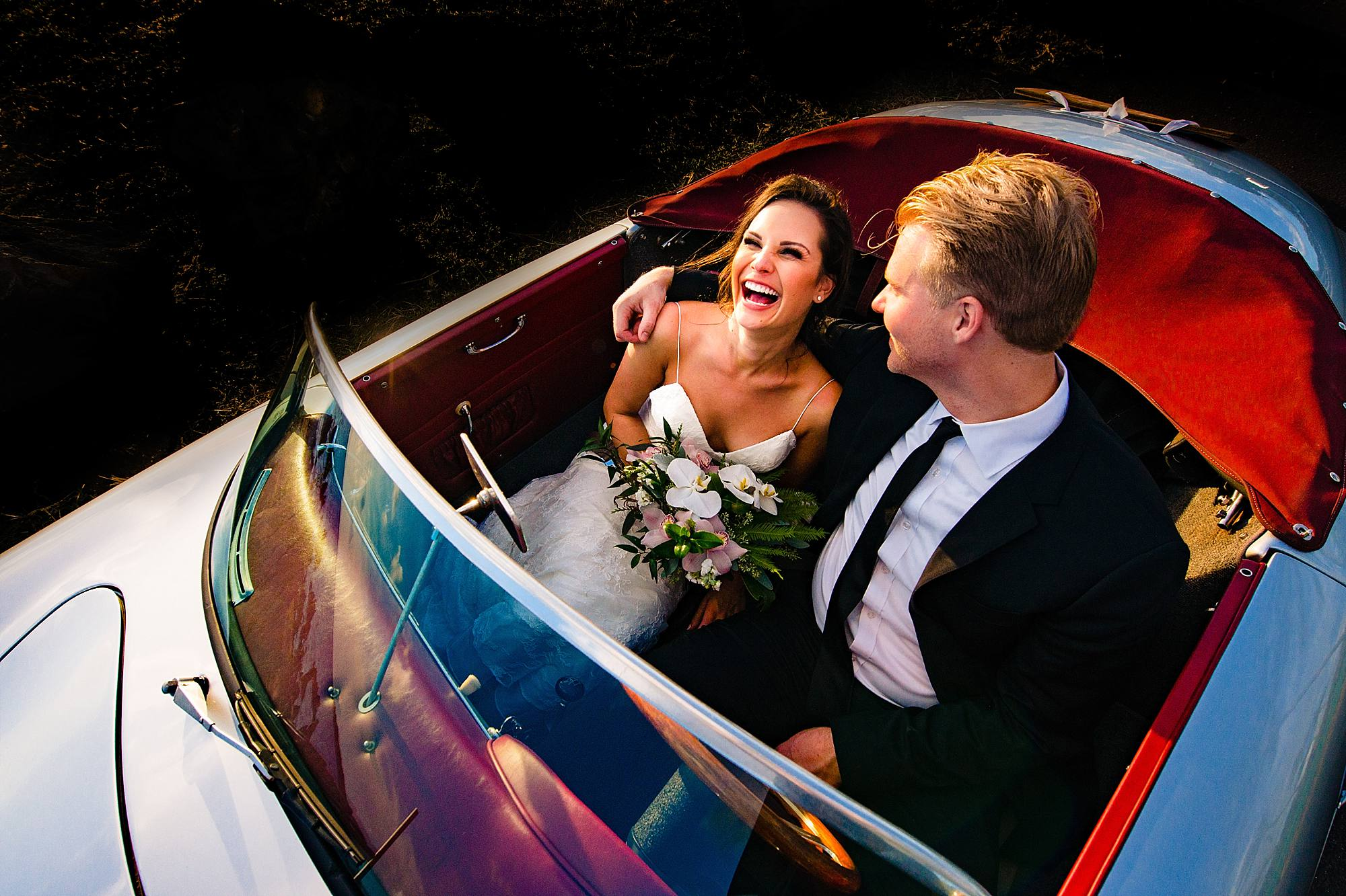 Happy couple exits in sports car - photo by Angela Nelson Photography