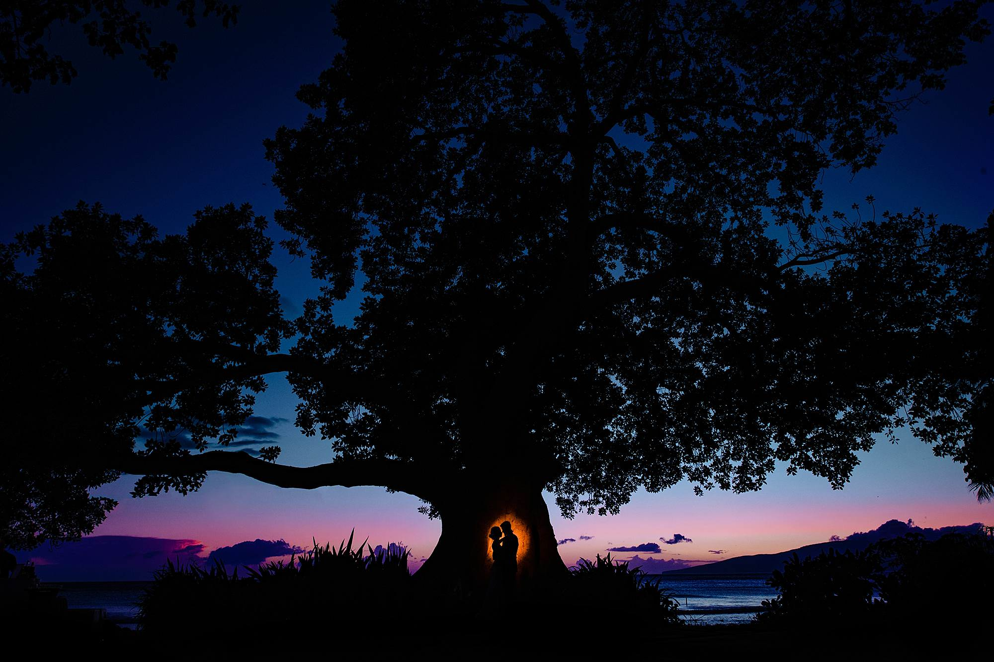 Maui couple silhouette with sunset and spotlight - photo by Angela Nelson Photography