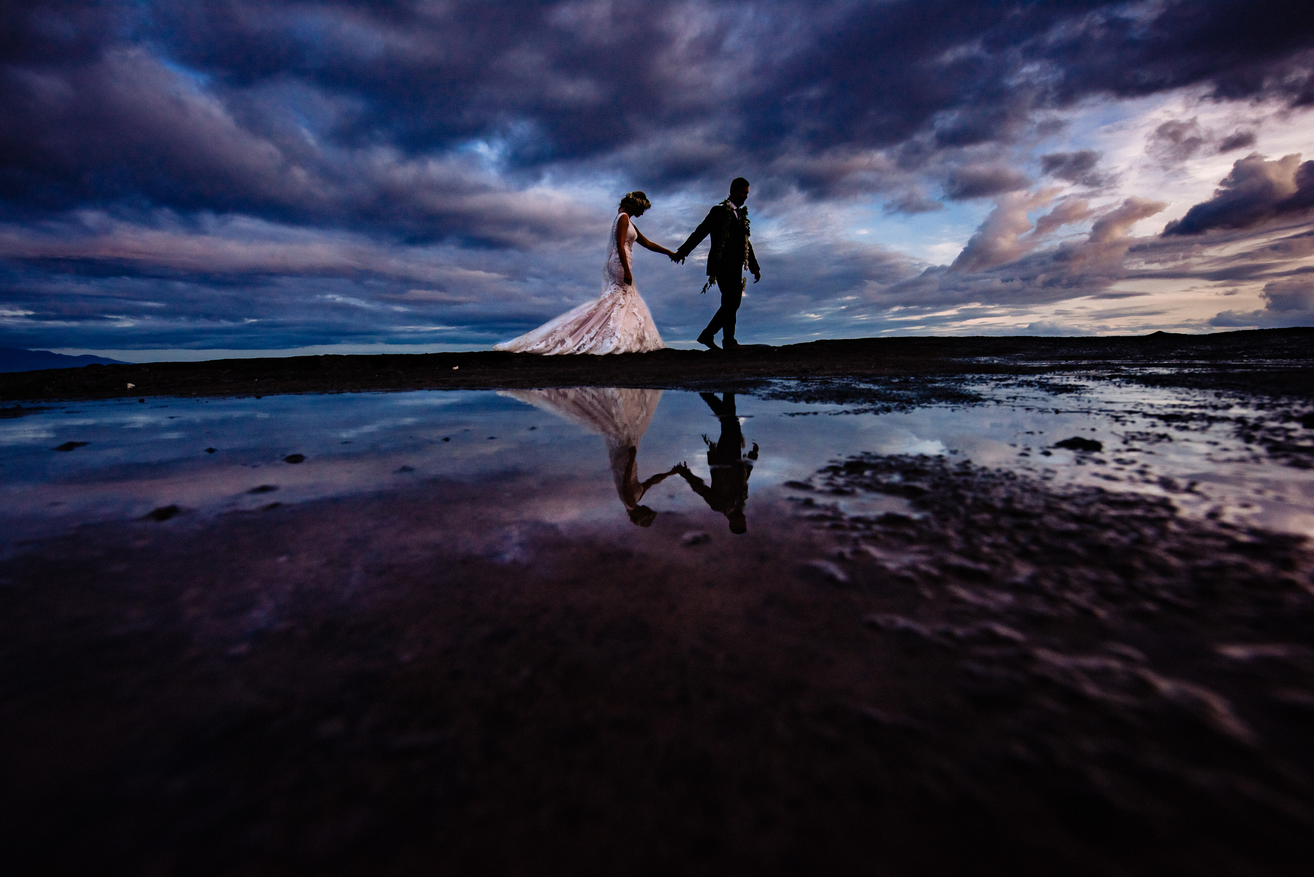 Reflected couple against stormy skies - photo by Angela Nelson Photography