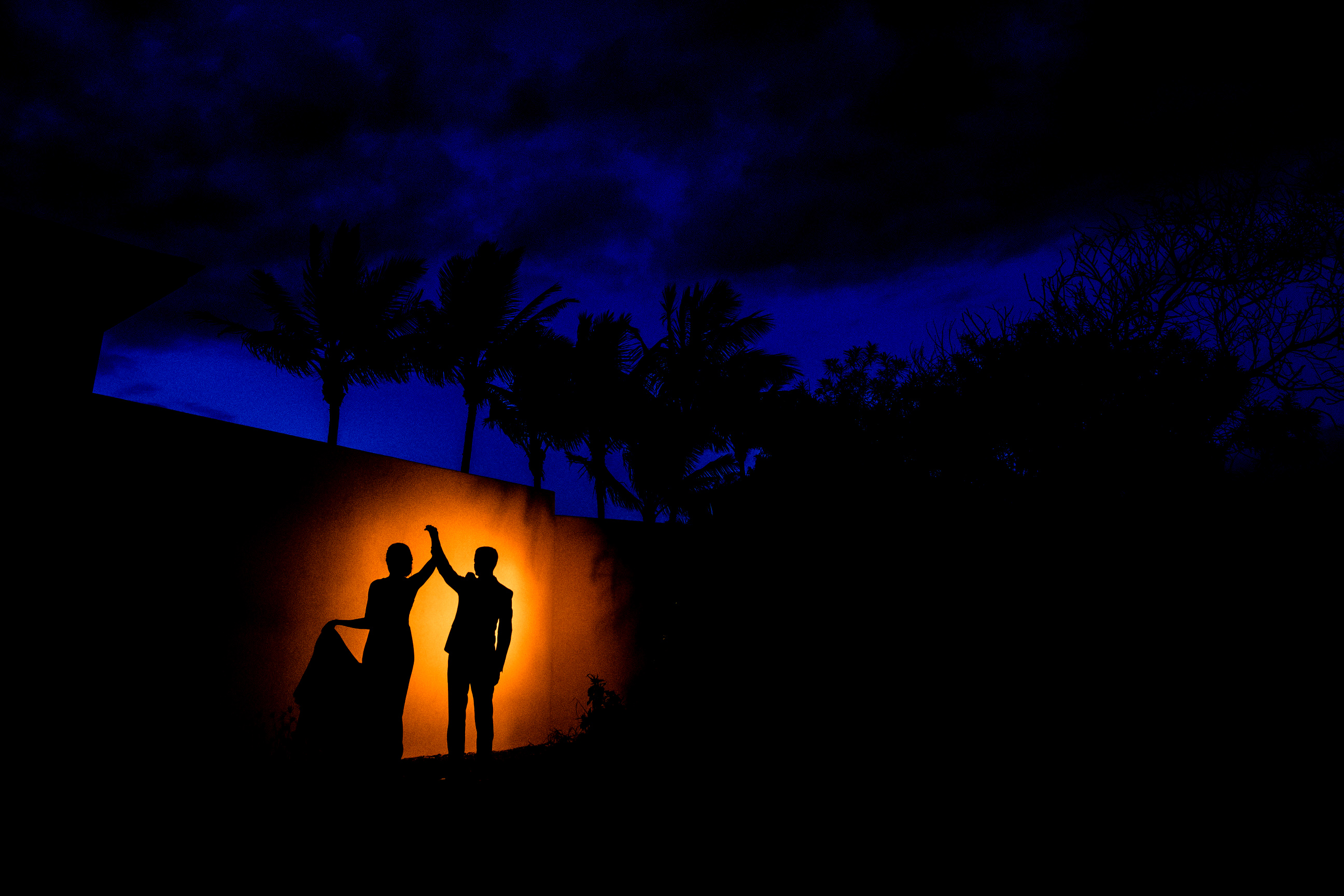 Silhouette couple against orange spotlight - photo by Angela Nelson Photography