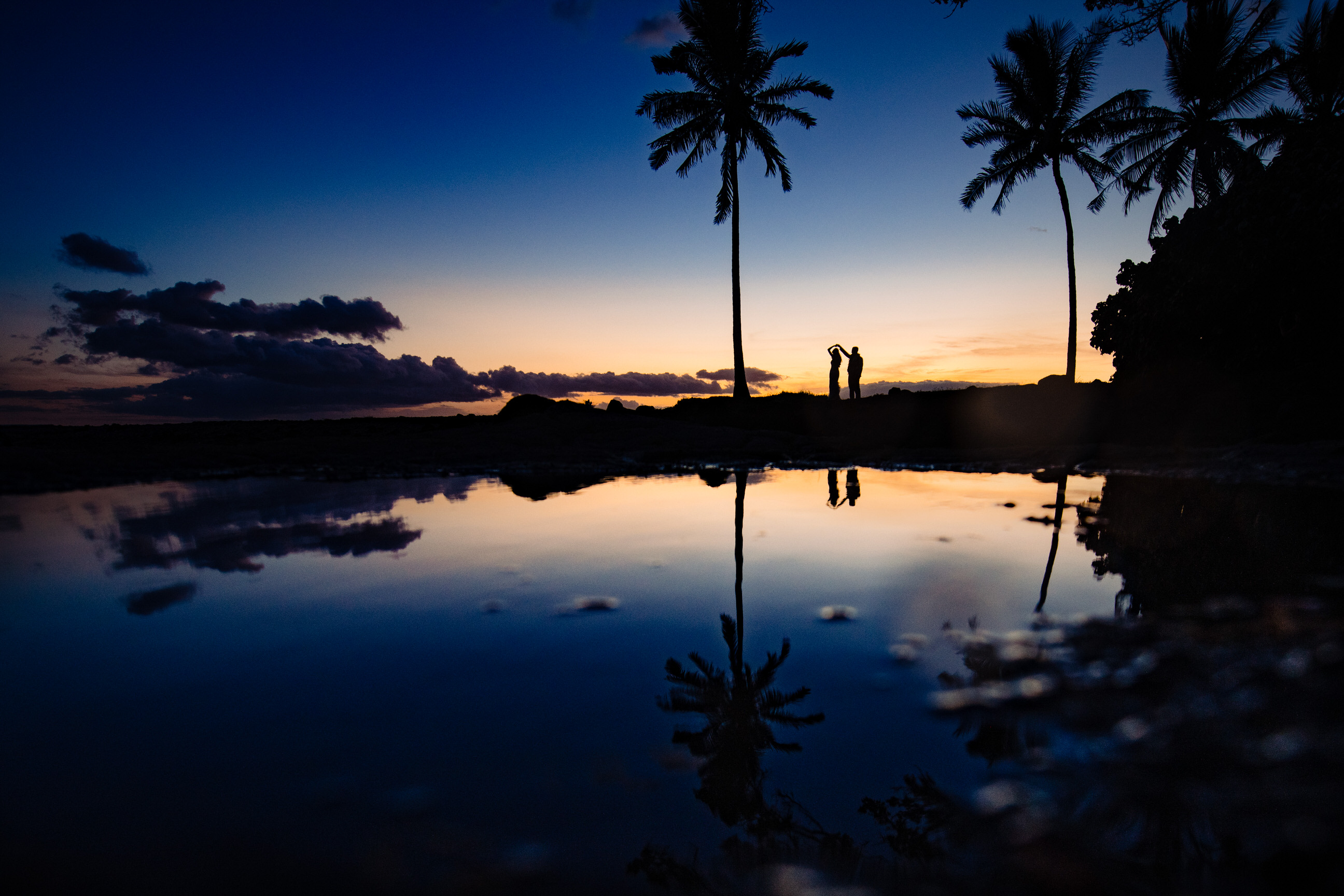 Silhouette couple against palm trees at sunset - photo by Angela Nelson Photography