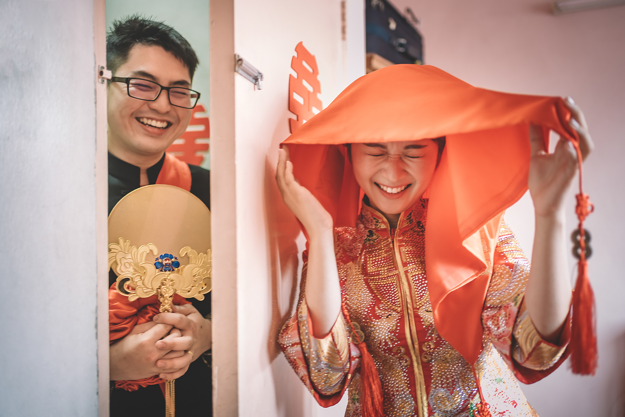 Asian bride hiding behind door from laughing groom - photo by Edwin Tan Photography