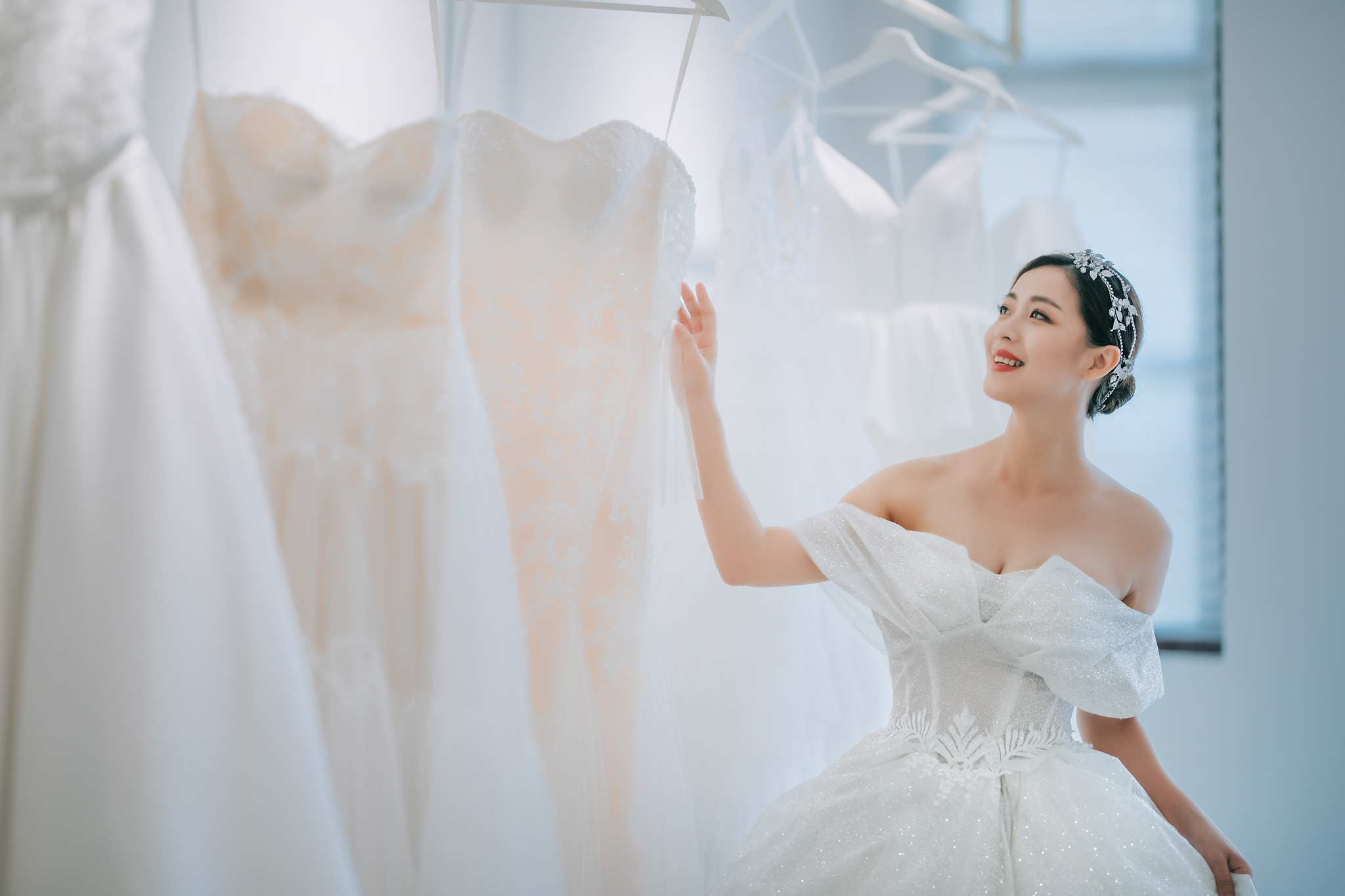 Asian bride in offshoulder corset lace gown among dresses - photo by Edwin Tan Photography