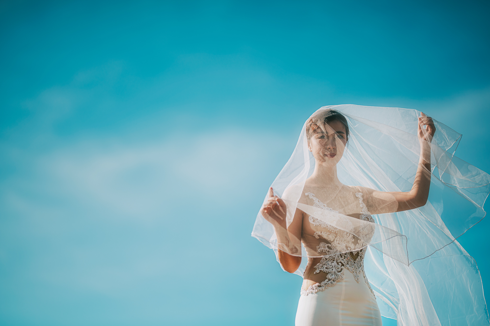Bride under veil against blue sky - photo by Edwin Tan Photography