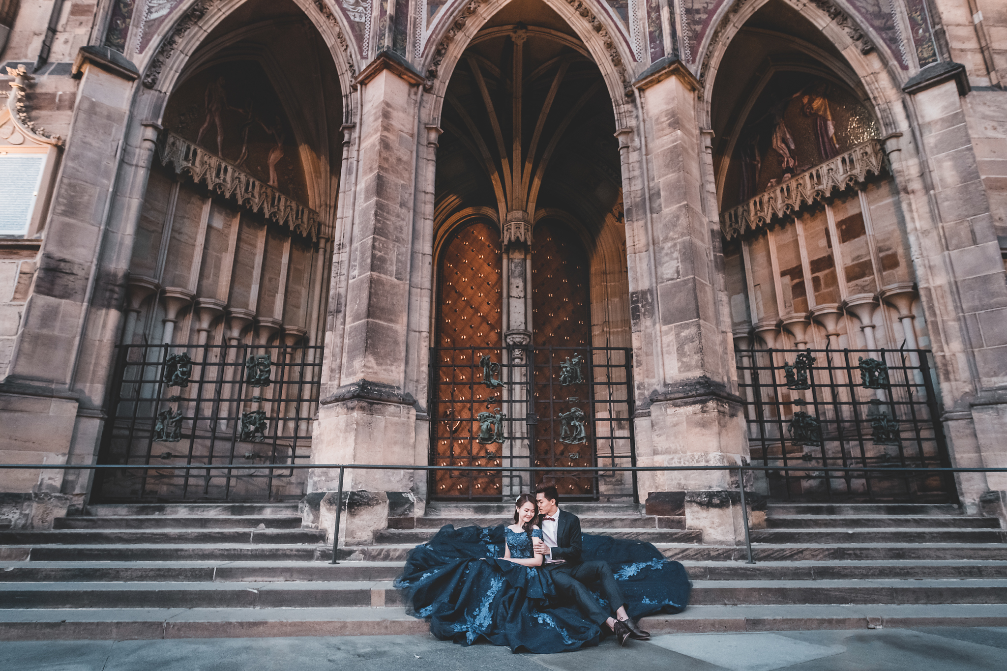 Bride wearing blue lace gown with groom outside of cathedral - photo by Edwin Tan Photography