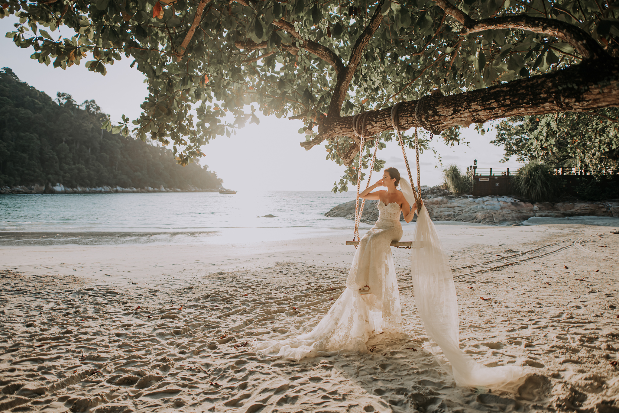 Bride with long lace gown and veil on beach front swing - photo by Edwin Tan Photography