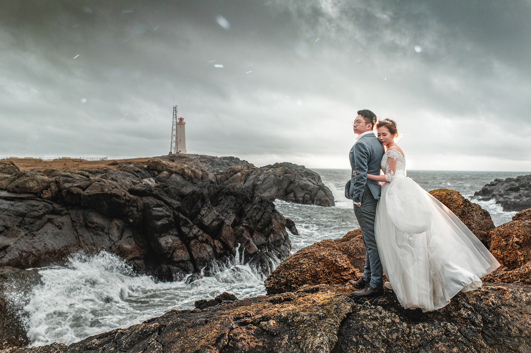 Couple portrait against crashing waves and lighthouse by Edwin Tan Photography