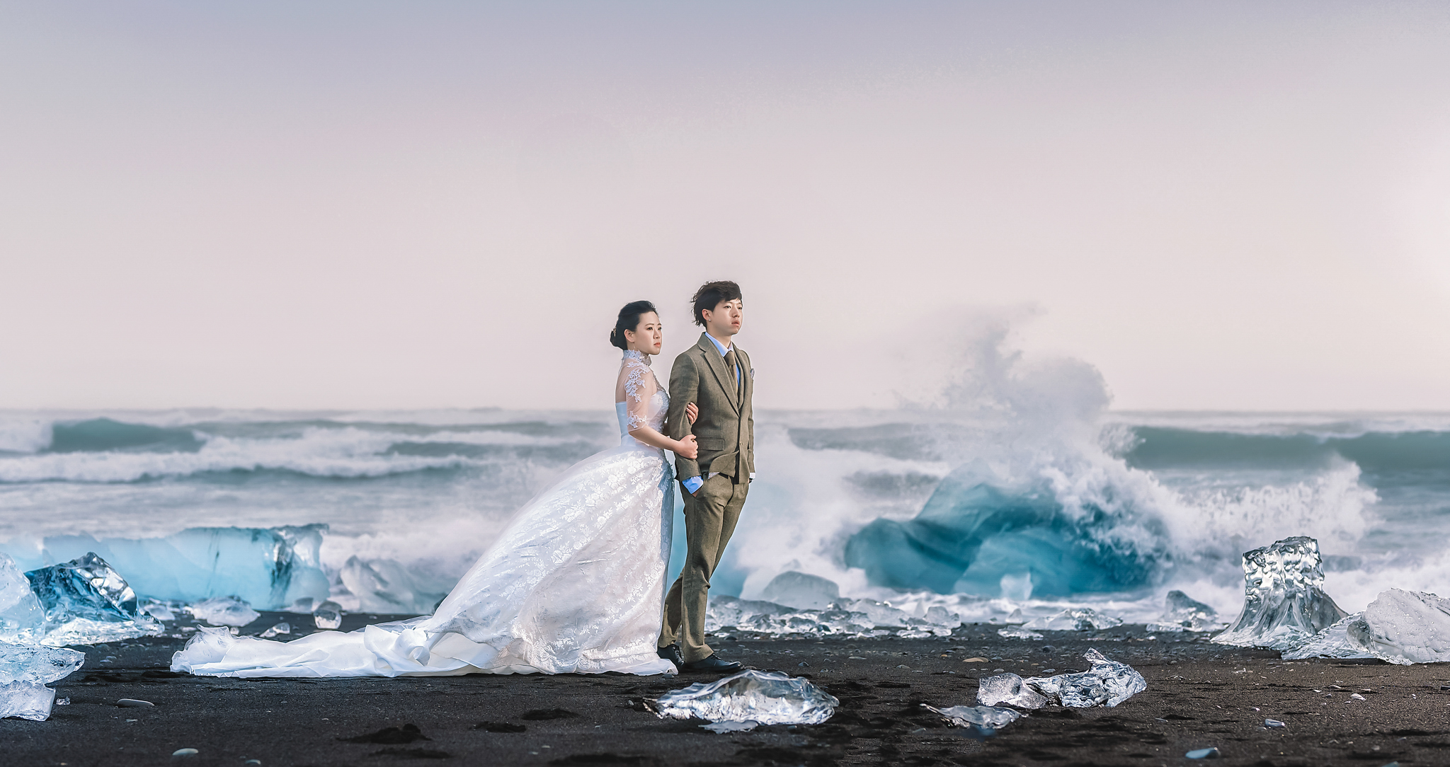 Couple with icebergs in front of ocean waves - photo by Edwin Tan Photography