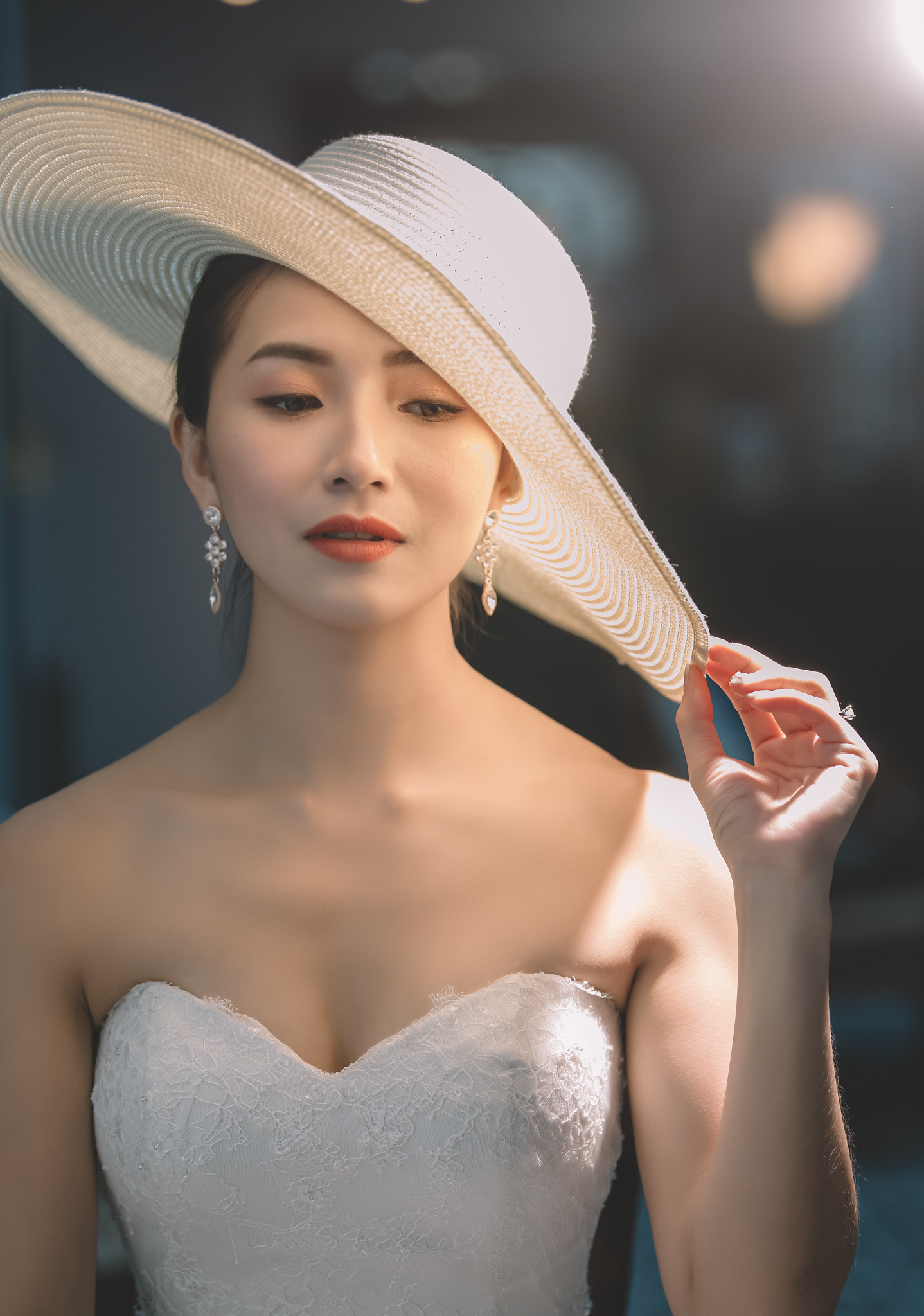 Bride with white brimmed hat and chandelier earrings - photo by Edwin Tan Photography