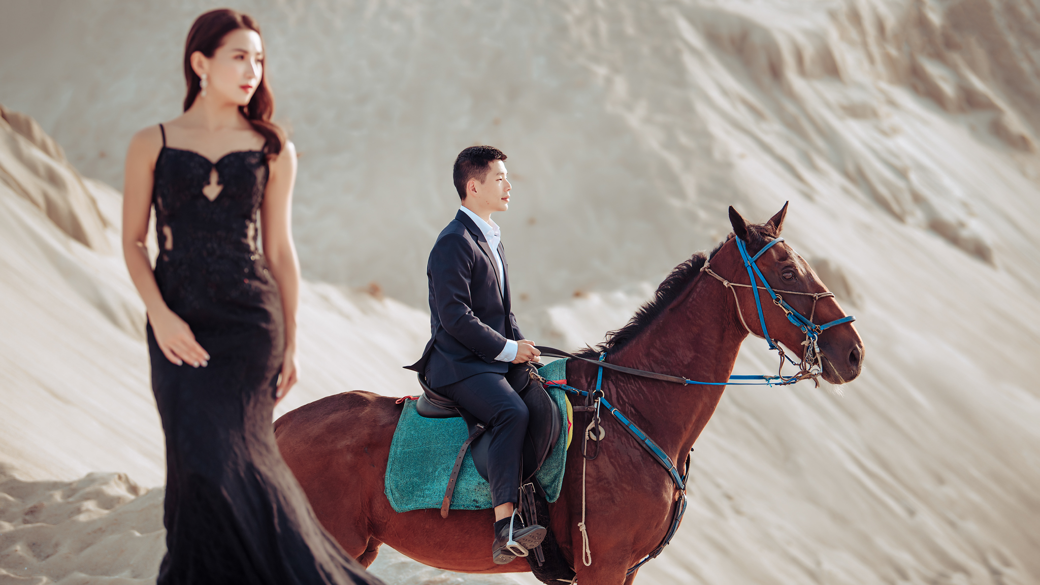 Engagement photo of groom on horse and bride in black cocktail dress by Edwin Tan Photography