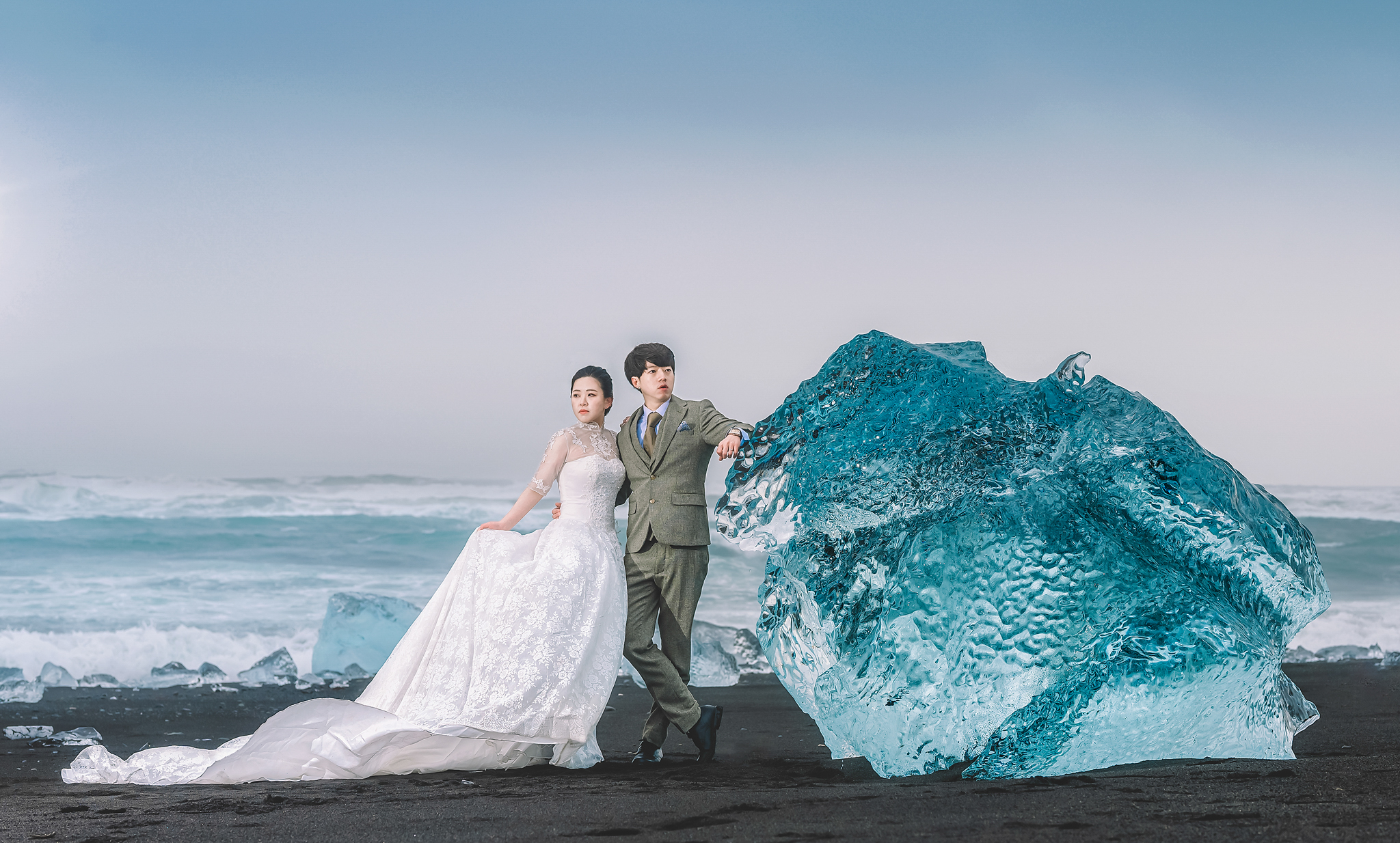 Fashionable Asian couple leaning against iceberg  - photo by Edwin Tan Photography