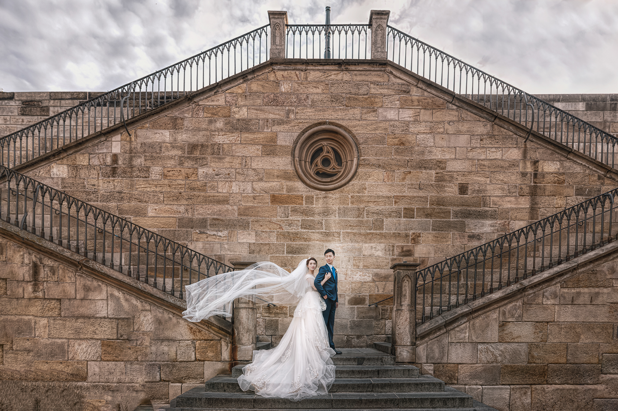 Fashionable couple portrait, bride with flowing veil on elaborate stone stairway by Edwin Tan Photography