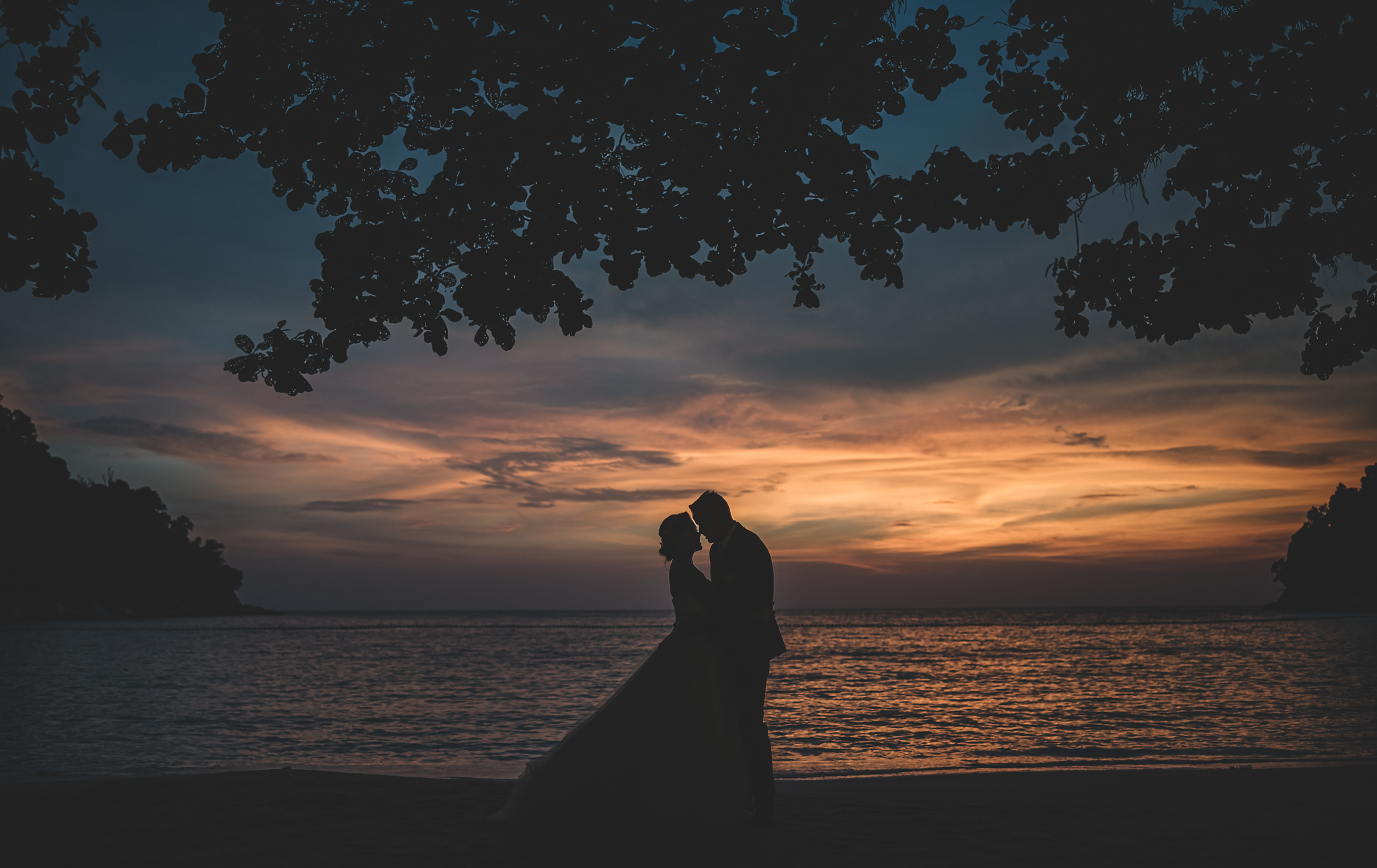 Silhouette of couple against golden beach sunset - photo by Edwin Tan Photography