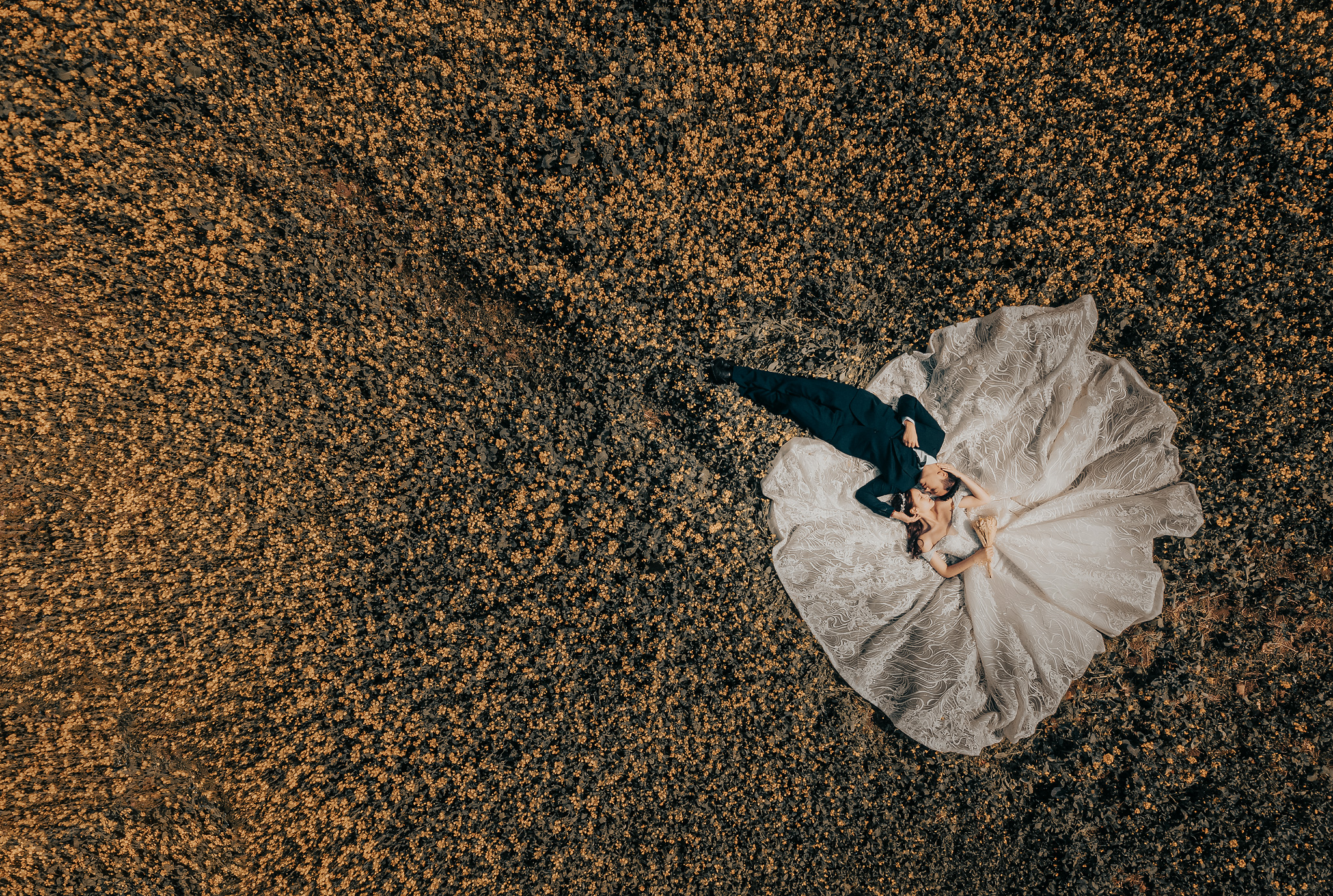 Aerial view of bride and groom laying in field - photo by Edwin Tan Photography