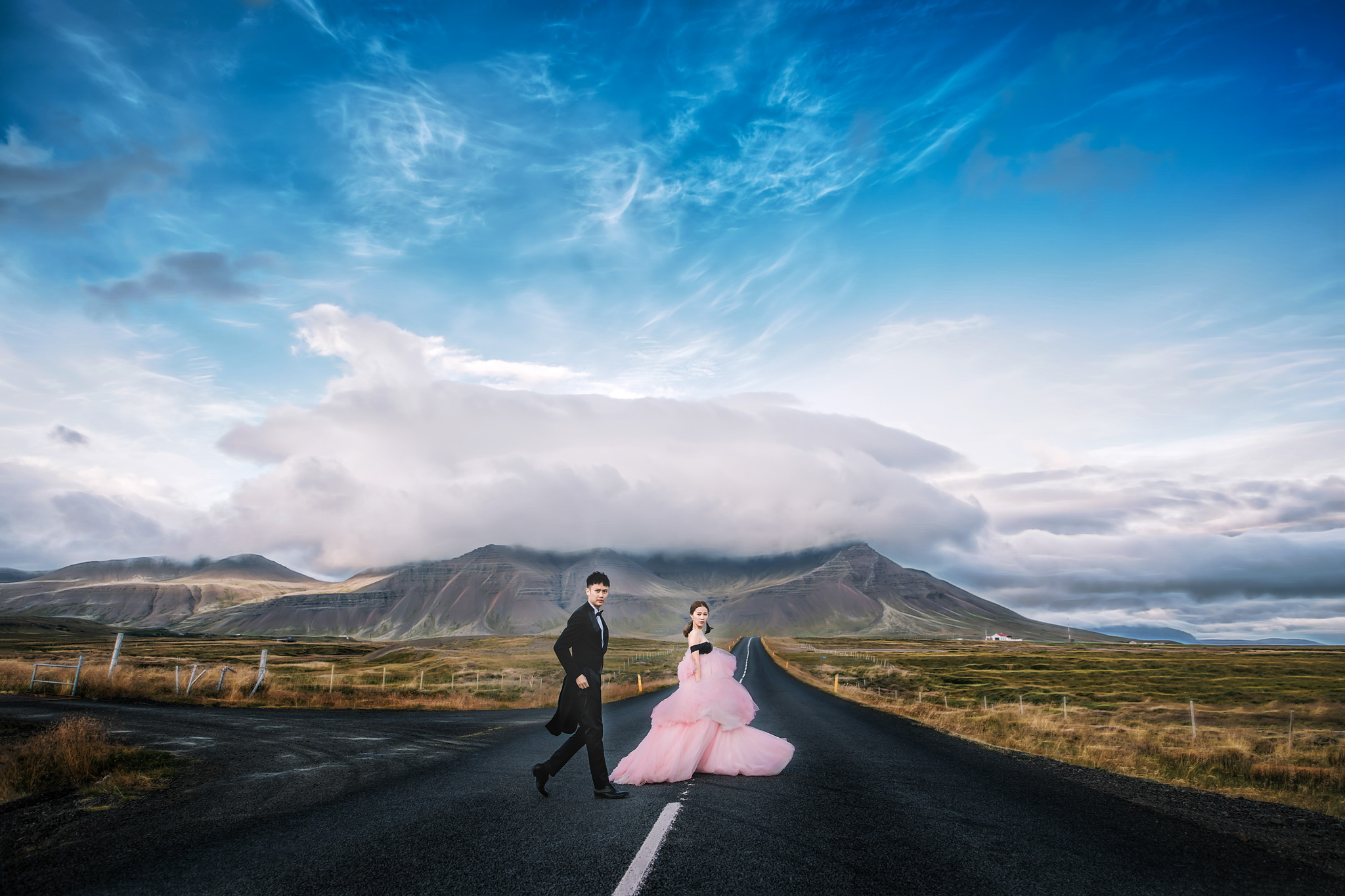 Bride and groom walking across road against hills - photo by Edwin Tan Photography