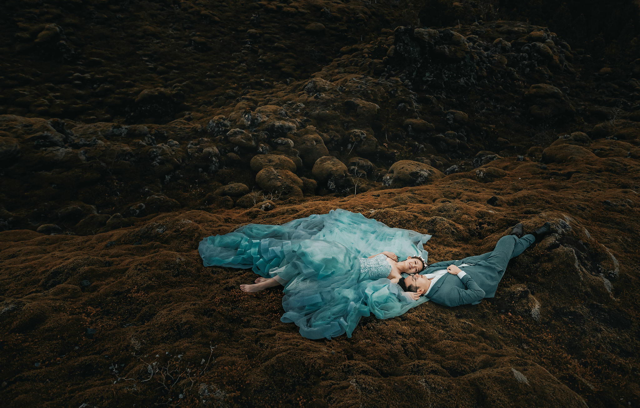 Bride in aqua gown lies beside her groom on tundra - photo by Edwin Tan Photography