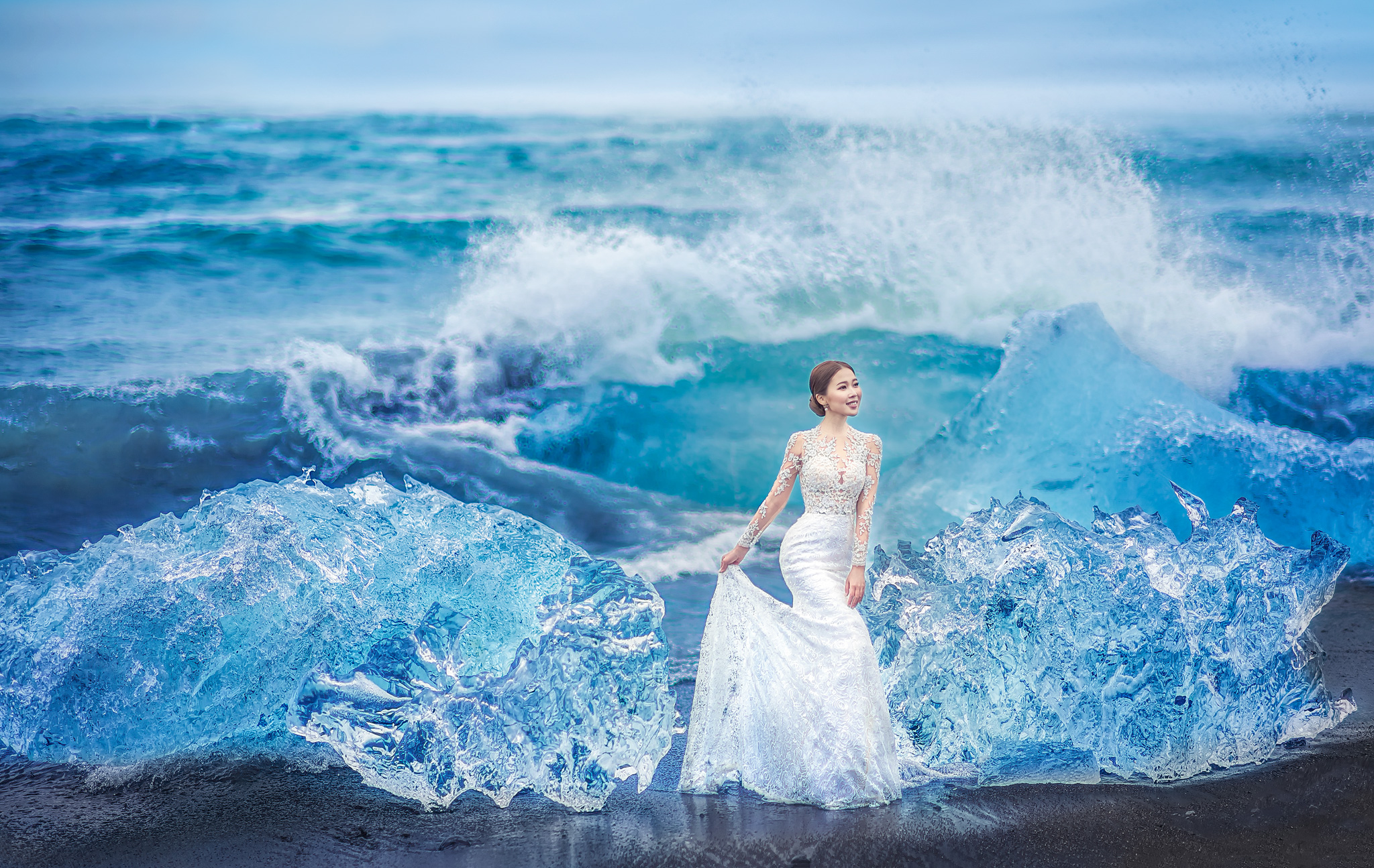 Bride in lace gown against crashing waves and ice - photo by Edwin Tan Photography