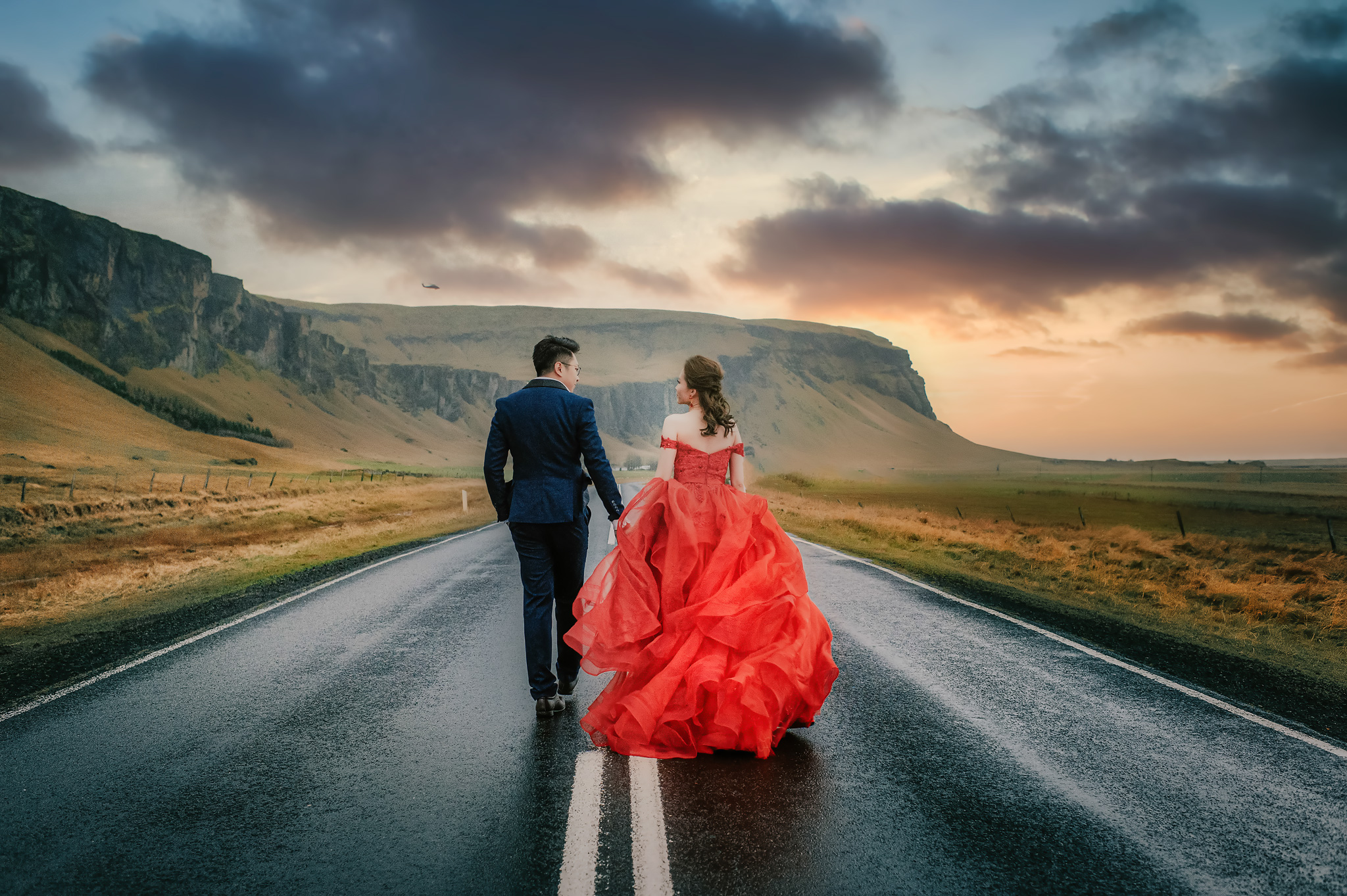 Bride in red gown and groom walking down countryside - photo by Edwin Tan Photography