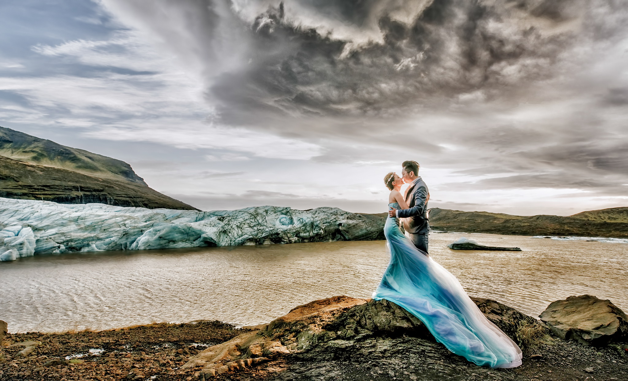 Bride with flowing blue dress and groom by glacier lake - photo by Edwin Tan Photography
