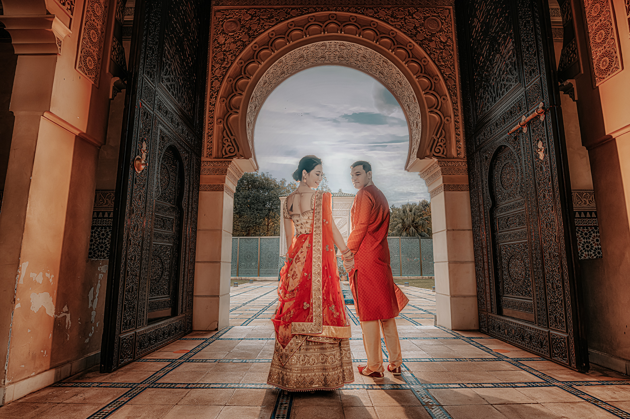 Couple in Indian wedding attire standing in historic site - photo by Edwin Tan Photography