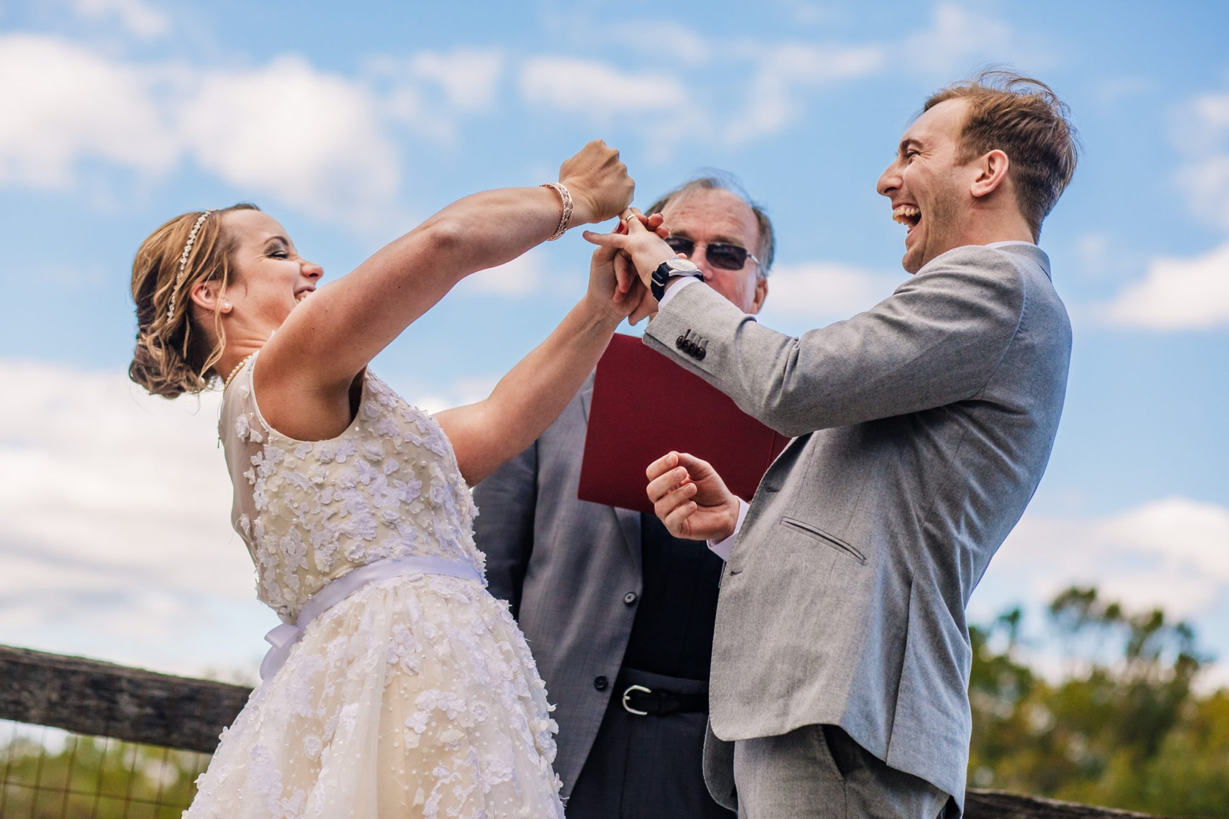 Bride and groom cheering at ceremony - photo by Photography by Brea