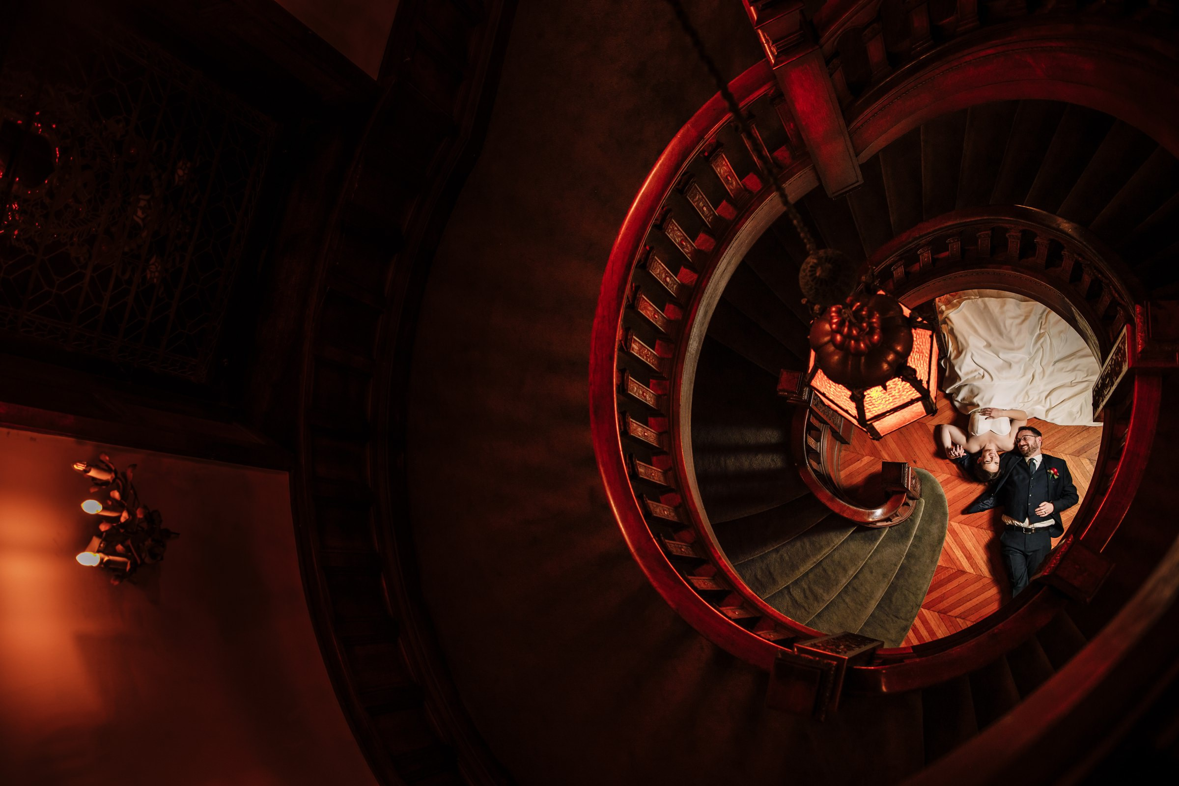 Bride and groom framed by spiral staircase - photo by Photography by Brea