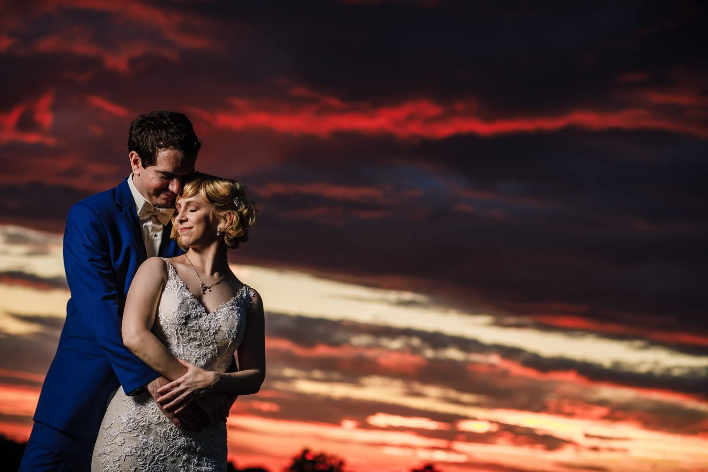 Bride and groom pose against sunset - photo by Photography by Brea