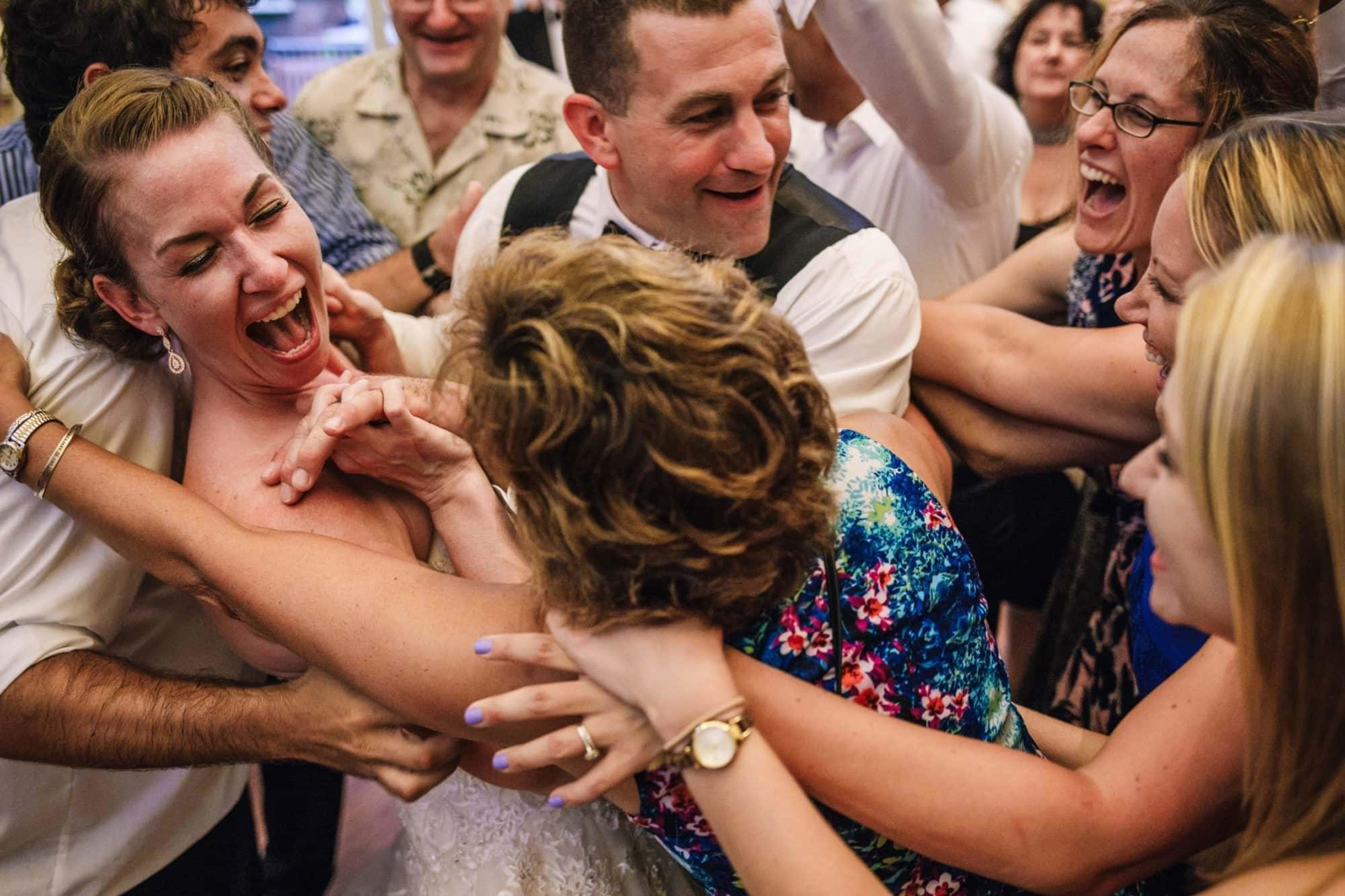 Bride and groom surrounded by guests - photo by Photography by Brea