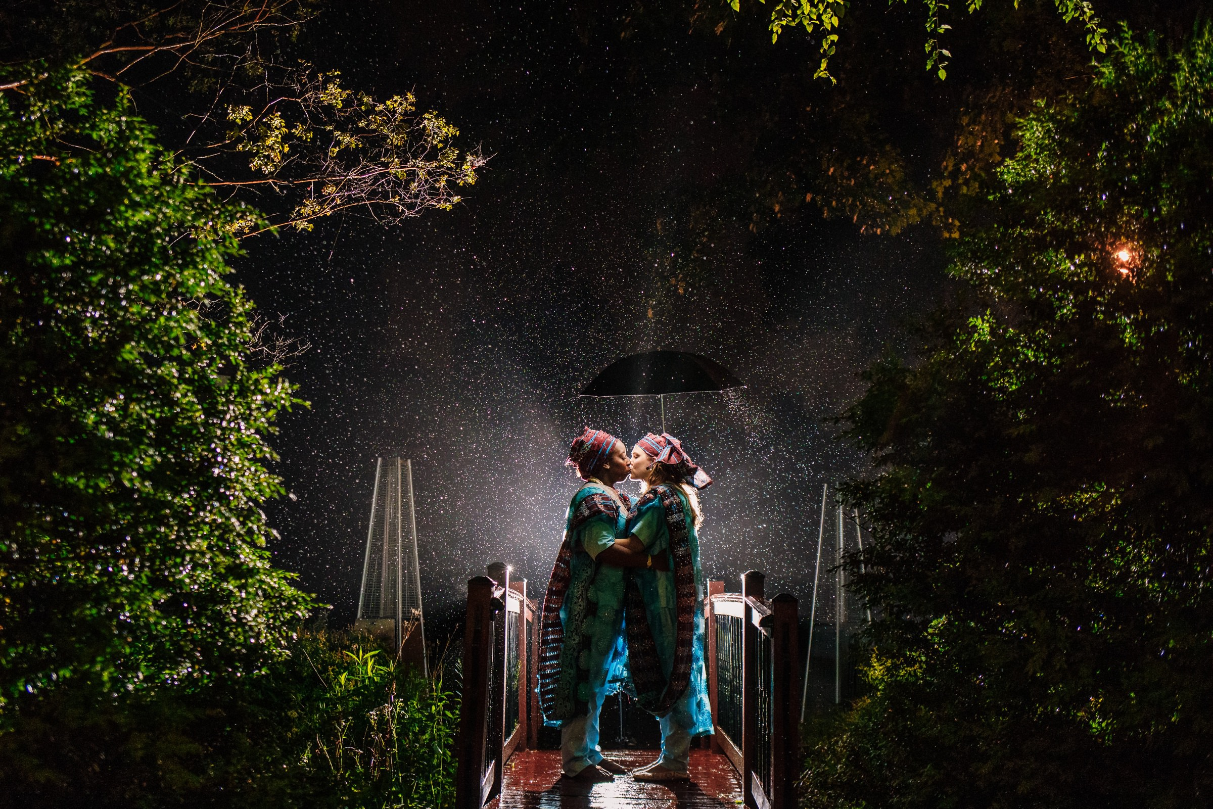 Brides kissing in the rain - photo by Photography by Brea
