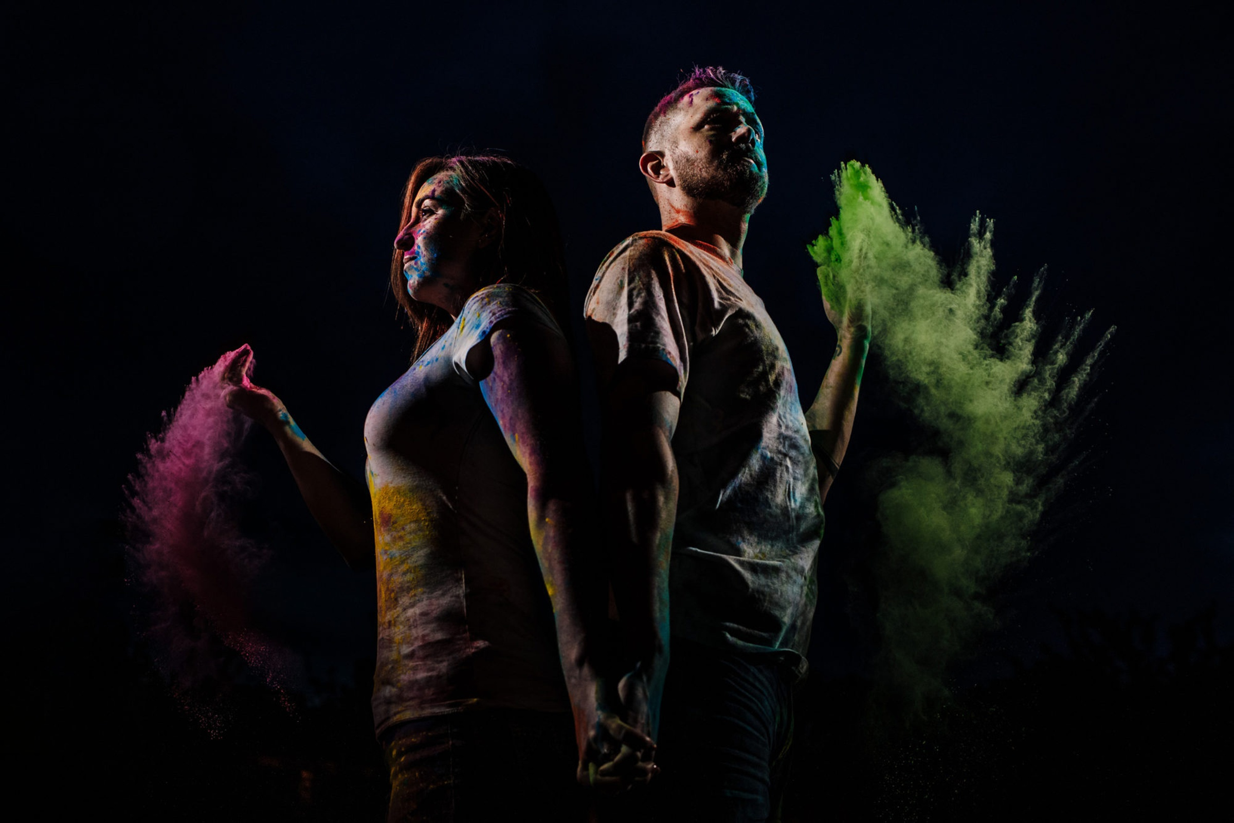 Dramatically lit engagement photo with color dust - photo by Photography by Brea
