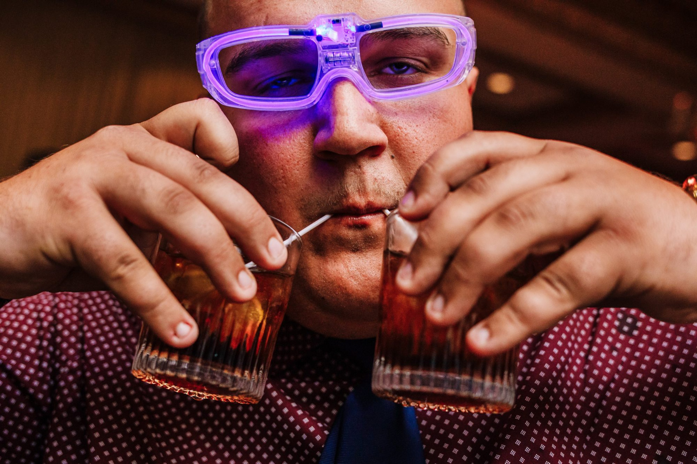 Guest with neon party glasses drinking - photo by Photography by Brea