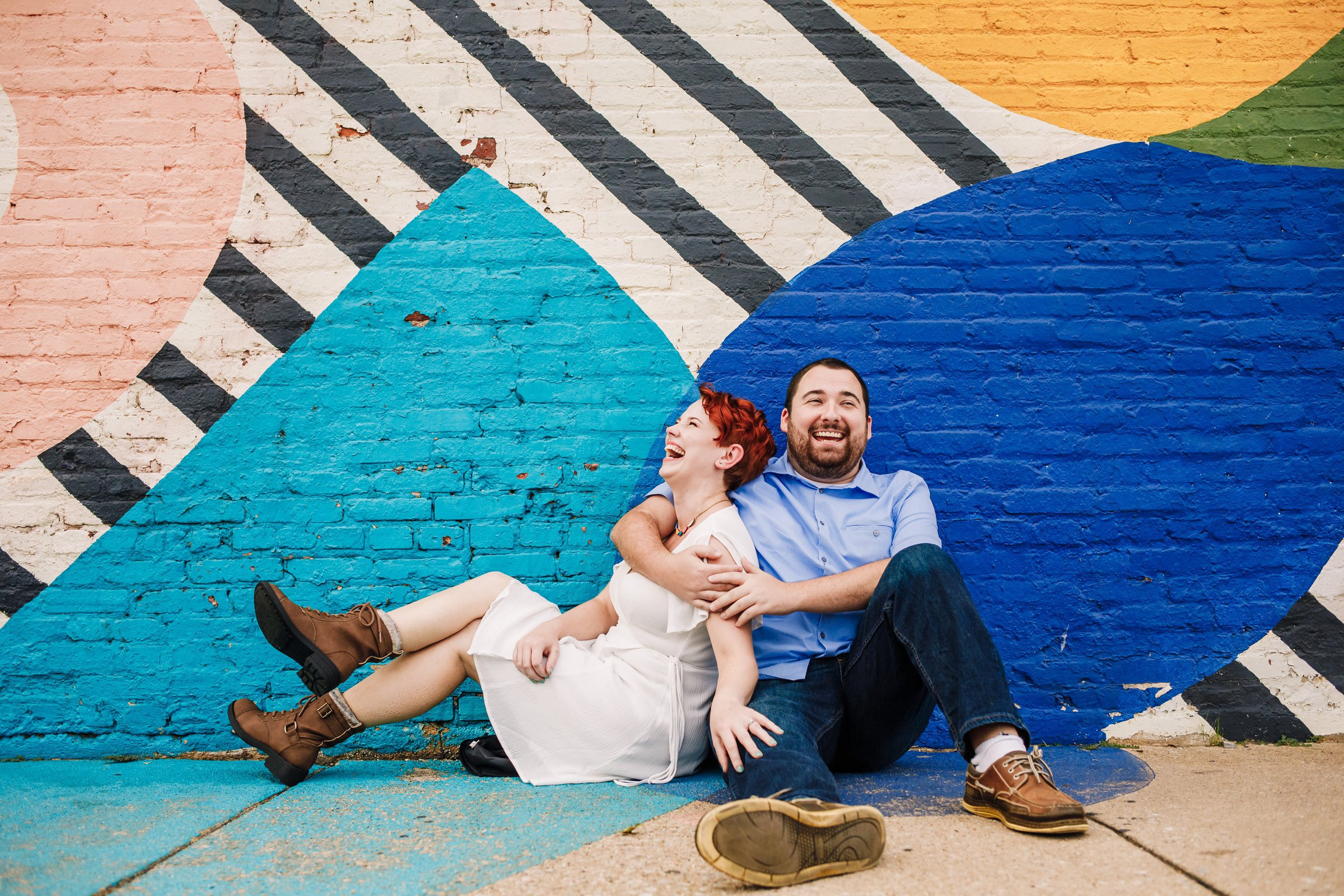 Laughing couple against colorful mural - photo by Photography by Brea