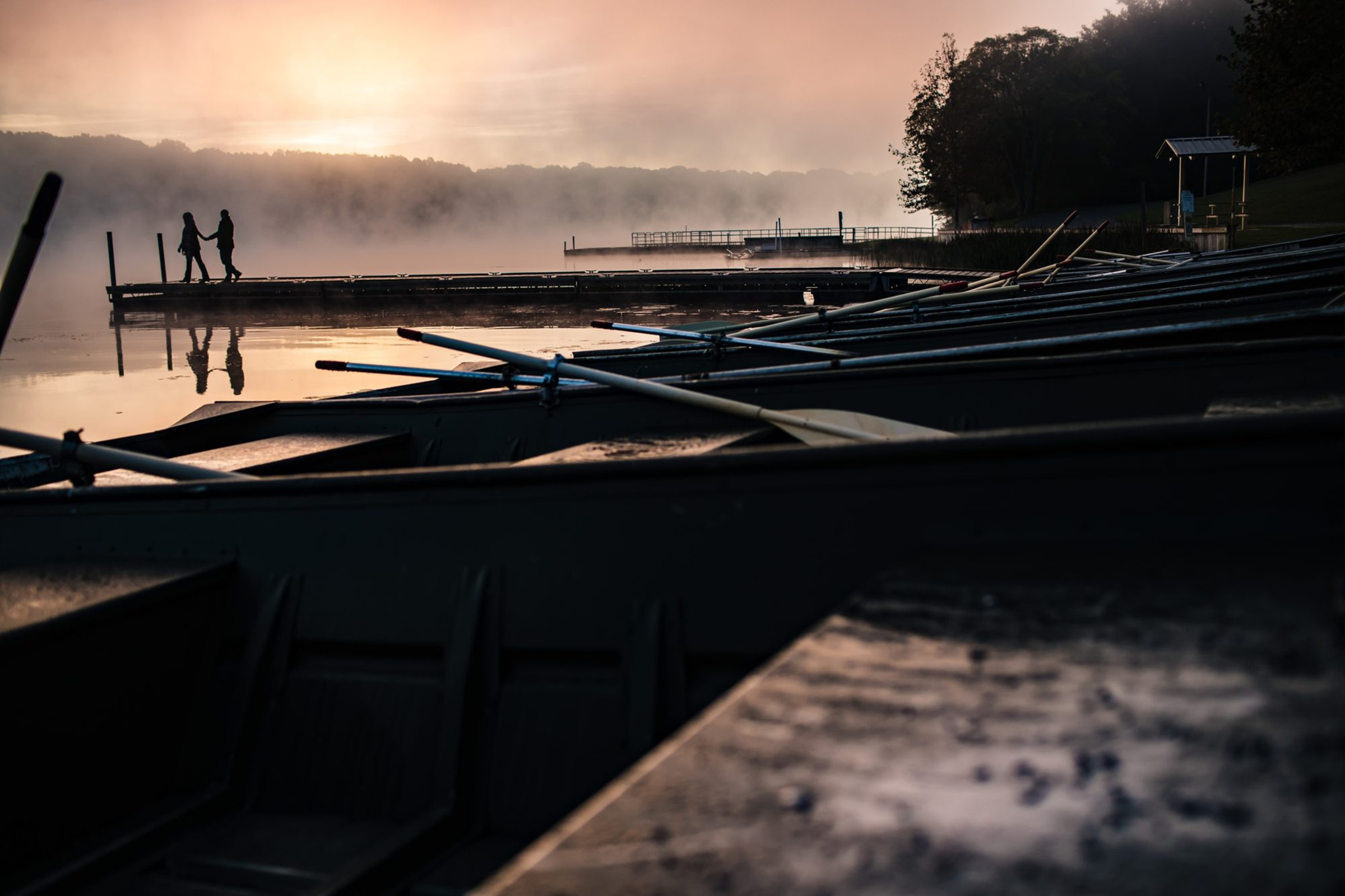Silhouette of couple with canoes in foreground at misty sunset - photo by Photography by Brea