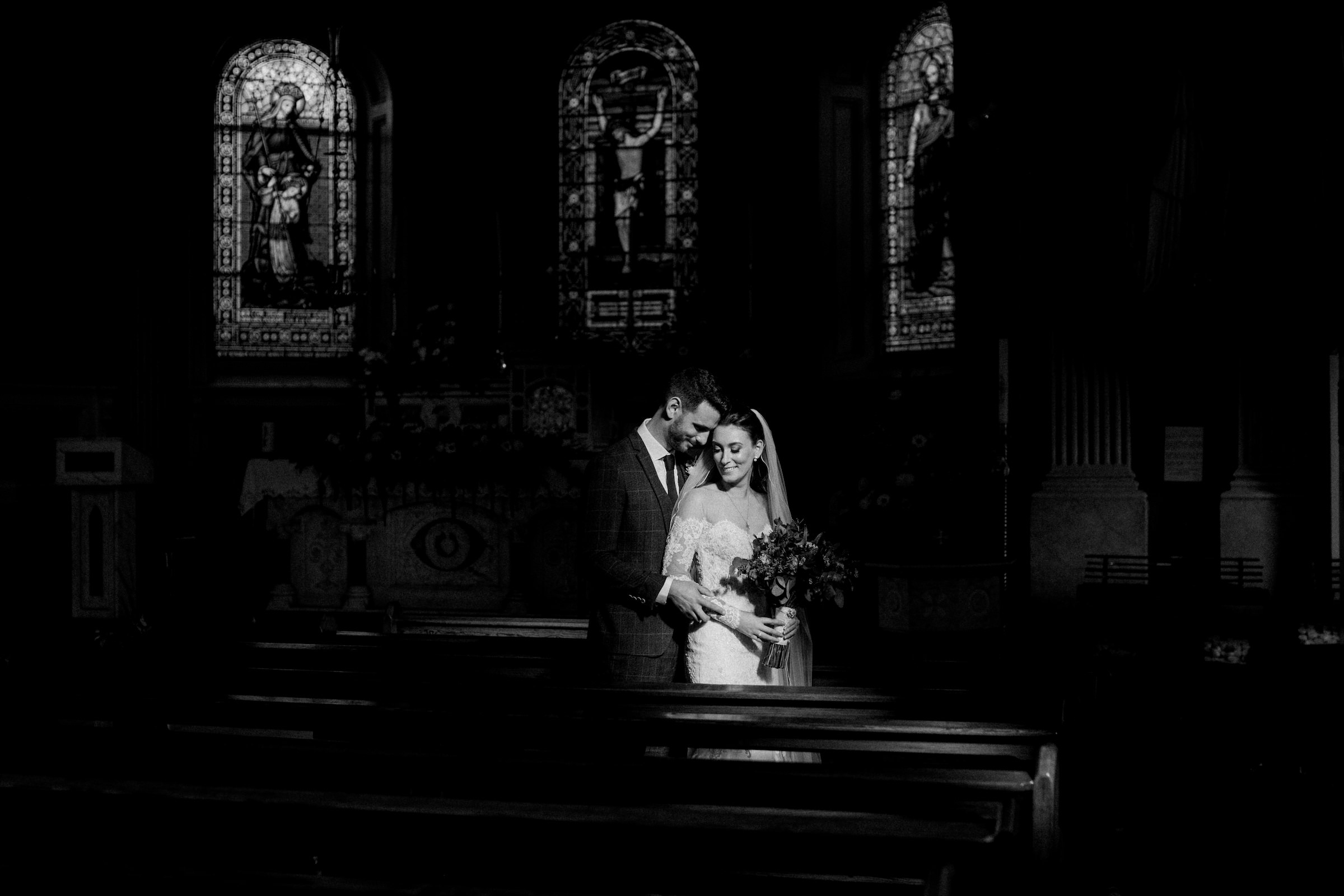 Bride and groom in bright windowlight at church - photo by White Cat Studio
