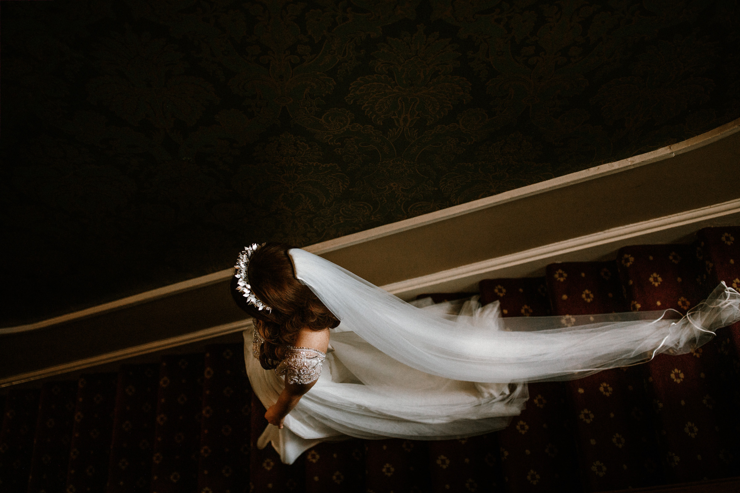 Bride descending stairs with tiara and long veil - photo by White Cat Studio