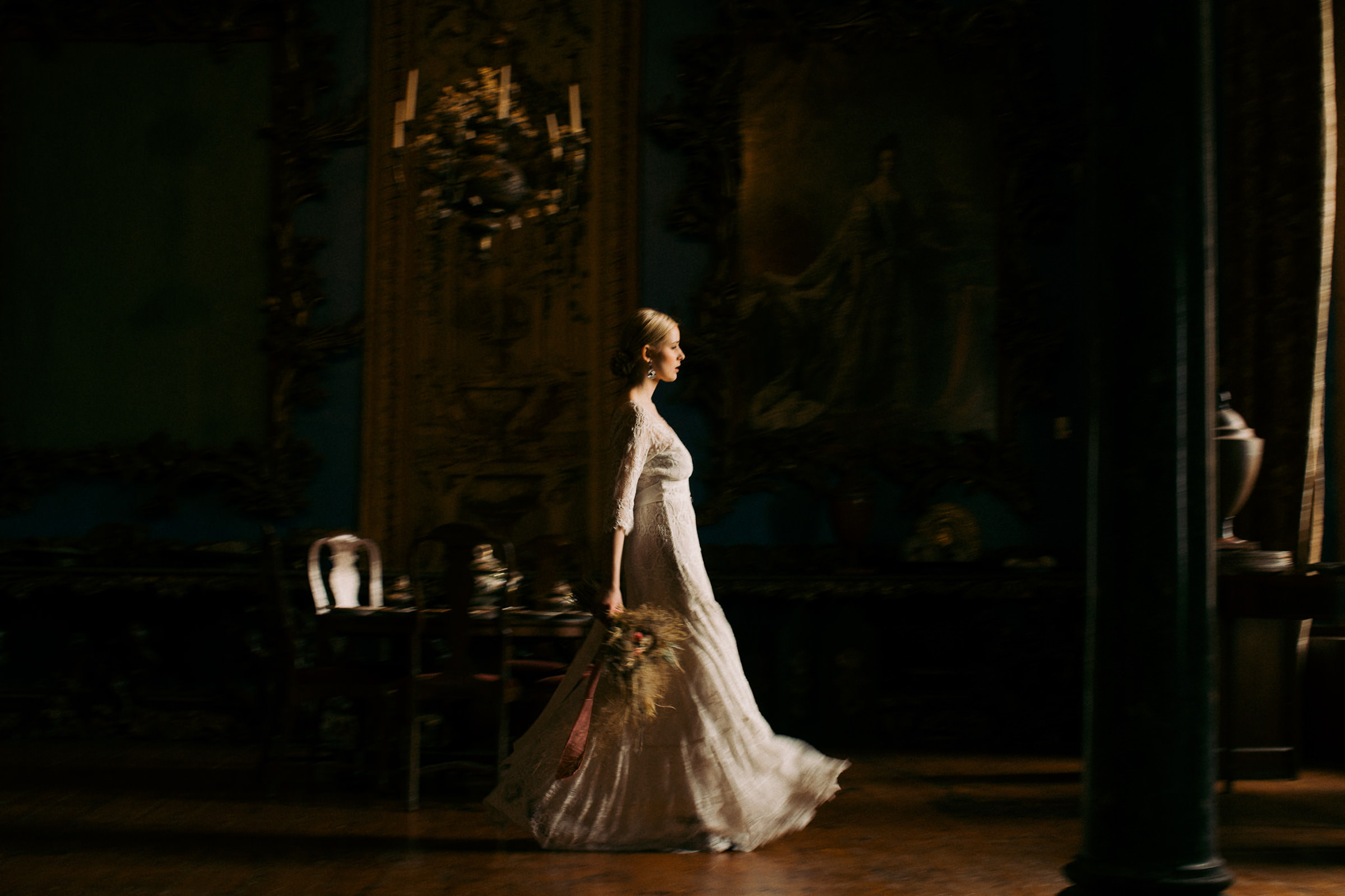 Bride in lace gown with 3/4 sleeves walks through old mansion -  photo by White Cat Studio