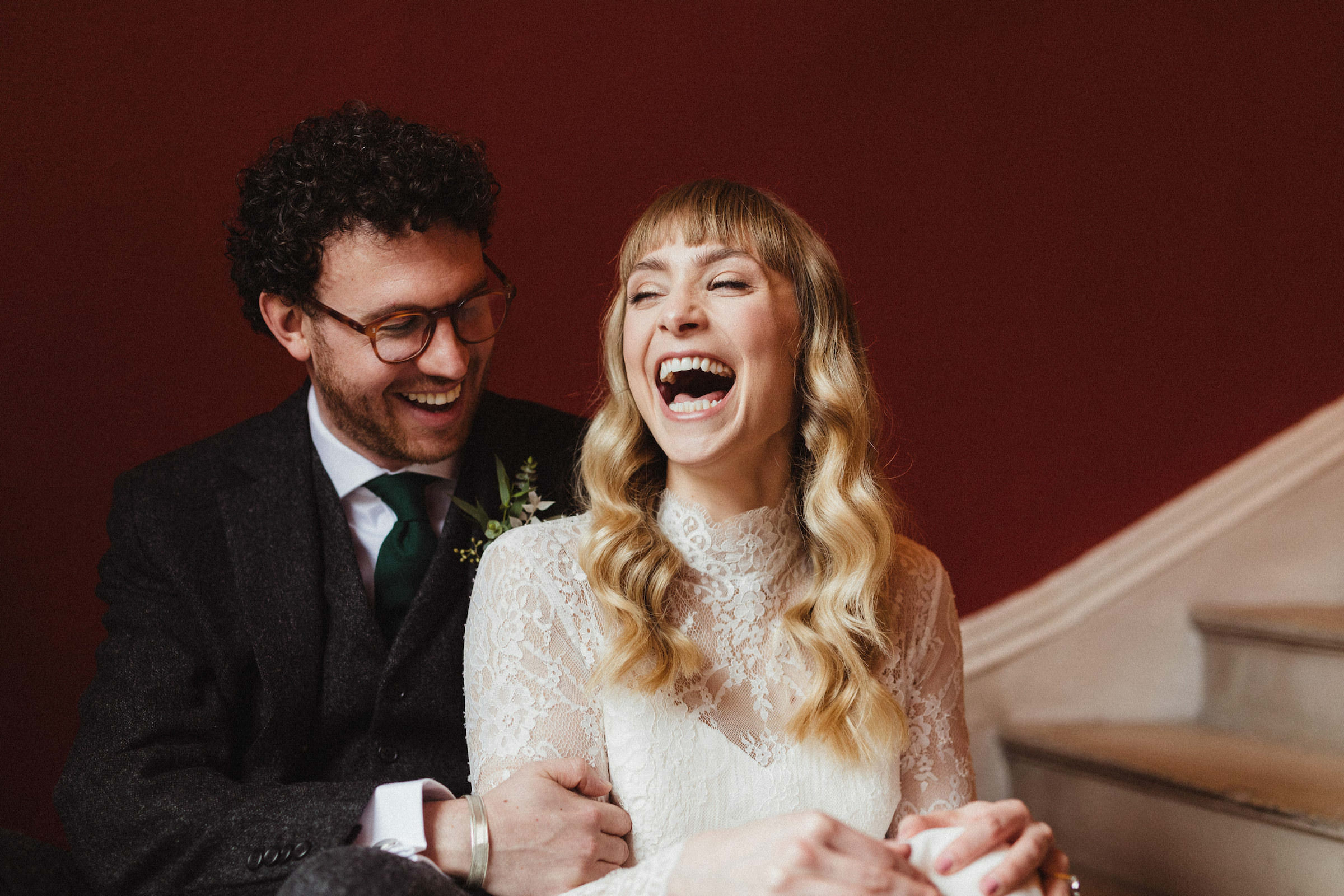 Bride in vintage lace dress and groom laughing - photo by White Cat Studio