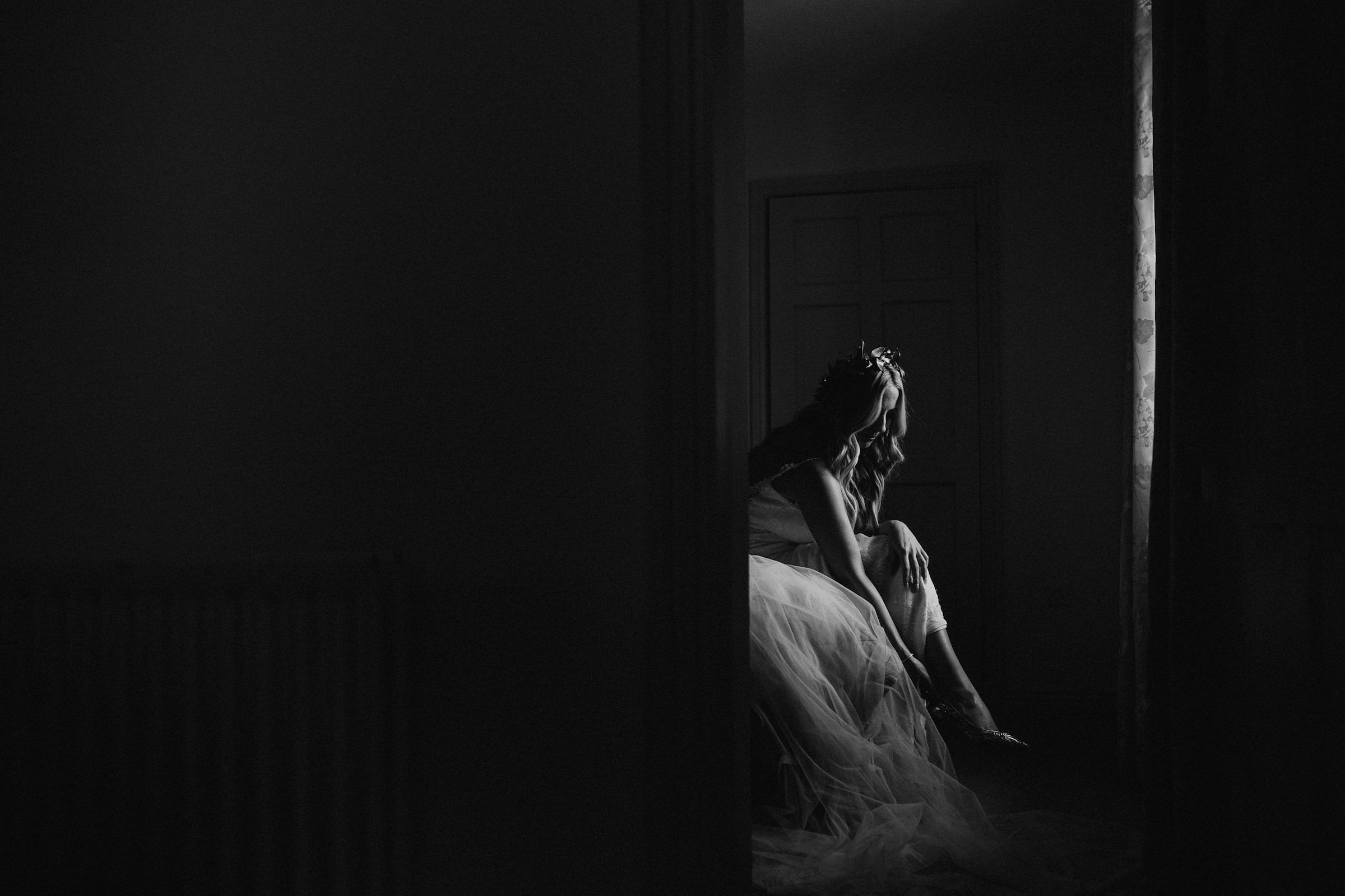 bride puts on her wedding shoes in dimly lit room  - photo by White Cat Studio