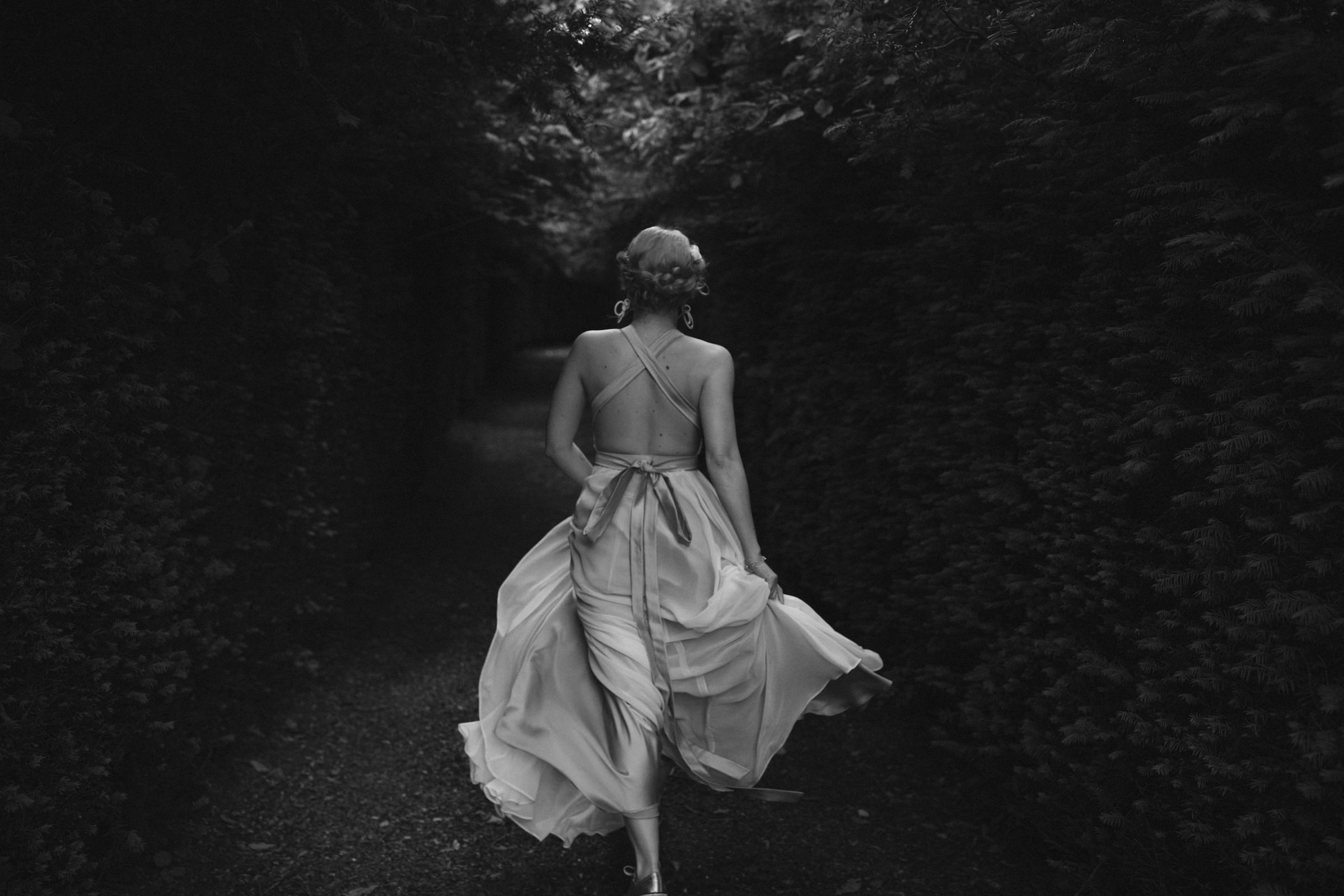 Bride walks away in silk dress with bow - photo by White Cat Studio
