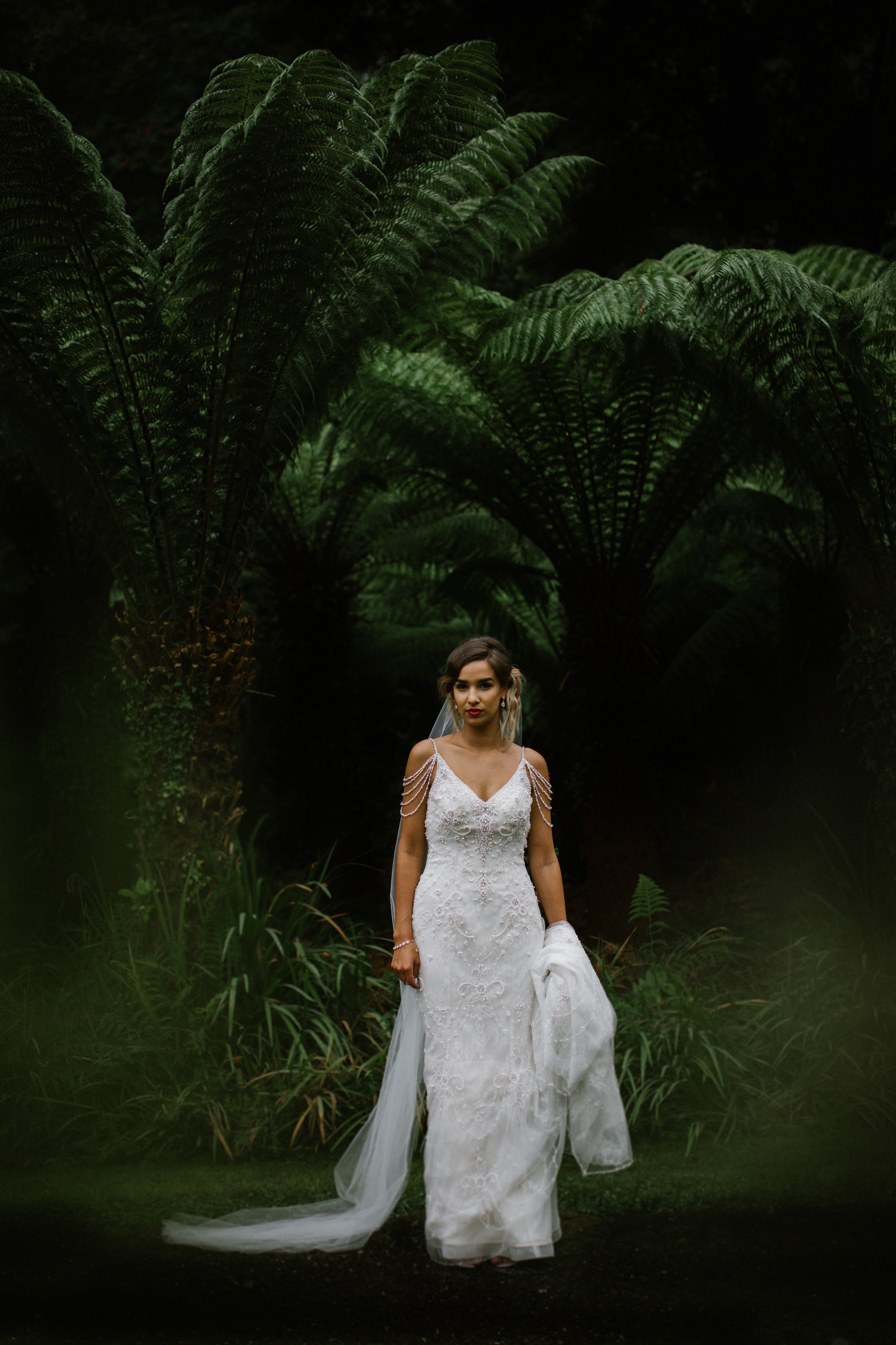 Bride wearing beaded spaghetti strap dress with draped jeweled shoulders - photo by White Cat Studio