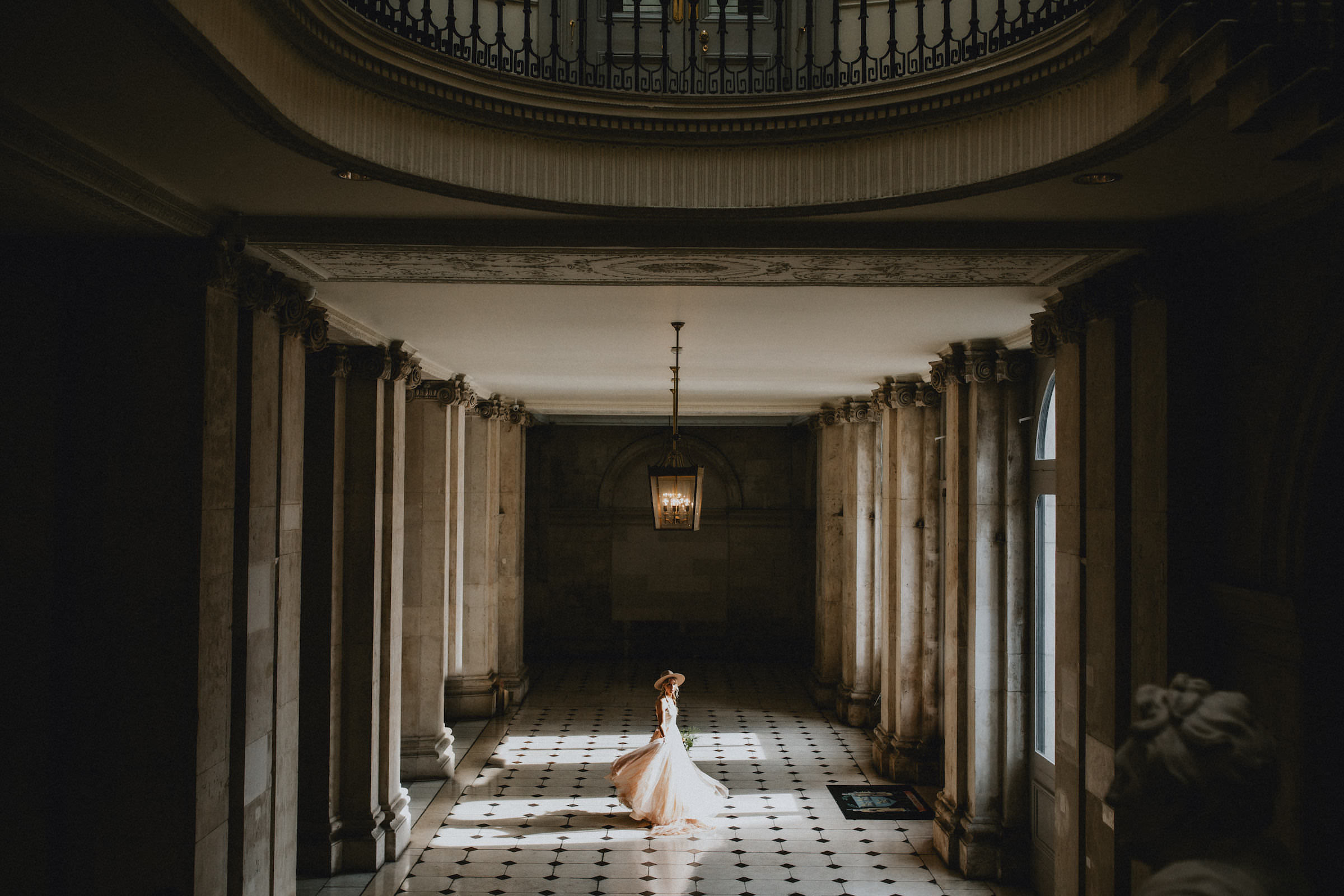 Bride with hat in blush chiffon dress  in tiled foyer - photo by White Cat Studio